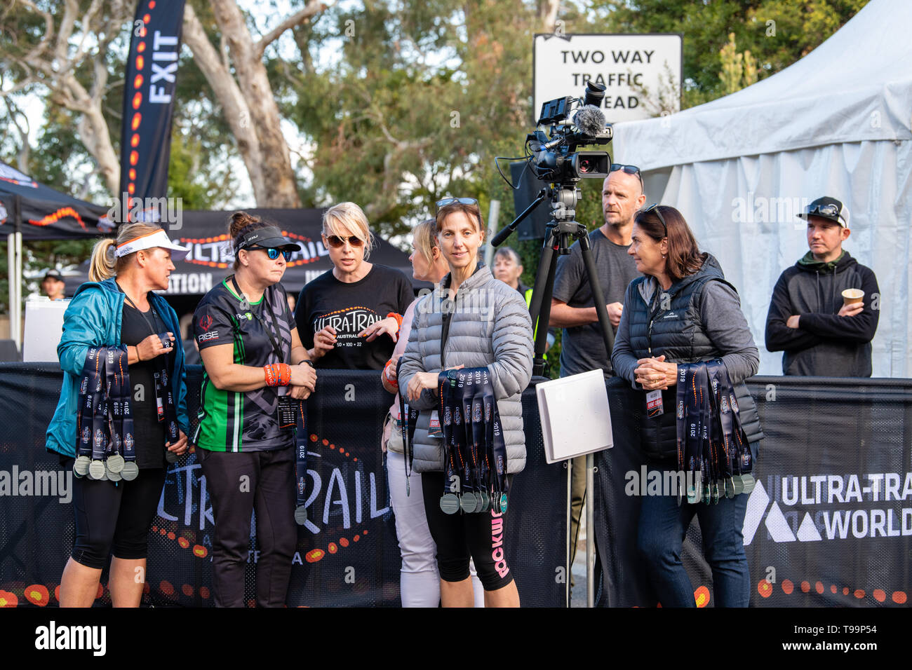 Blue Mountains, Australia - April 16 2019: Ultra-Trail Australia UTA11 race. Volunteers handing out medals at the finish line. Stock Photo