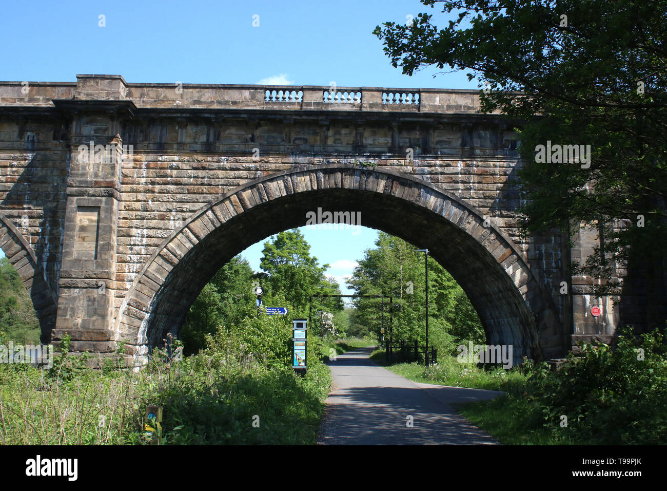 View along the Lune Valley Ramble as it passes under the Lune Aqueduct in Lancaster, Lancashire, England on the track bed of an old railway line. - Stock Image