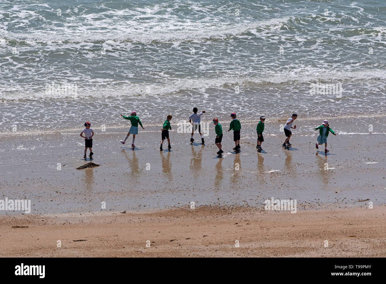 Southsea, Portsmouth, England, UK. May 2019.  A line of school children playing on the  beach with a backdrop of waves at Southsea an English resort. - Stock Image