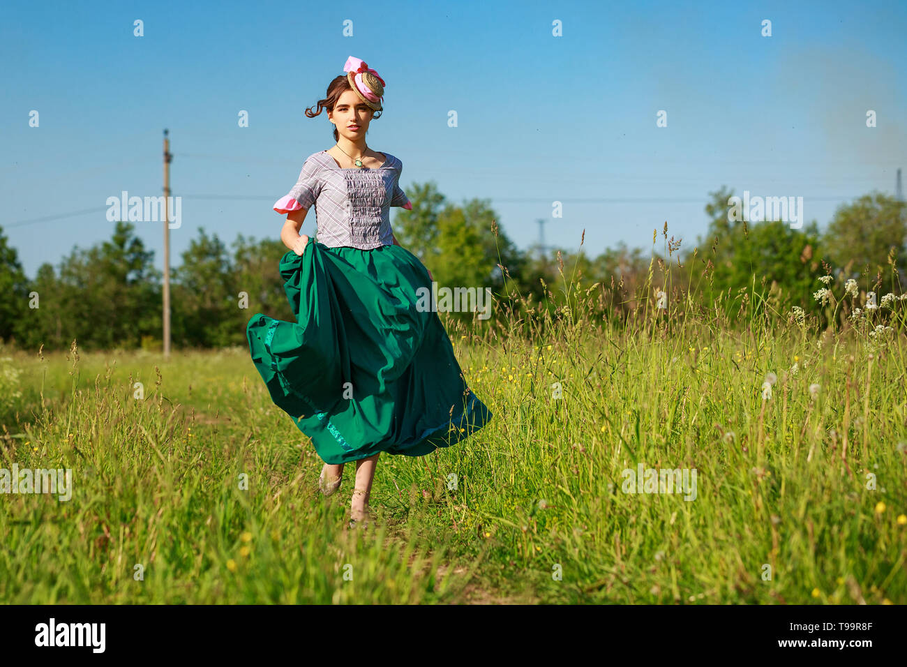 beautiful woman in dress in nature running on the road Stock Photo