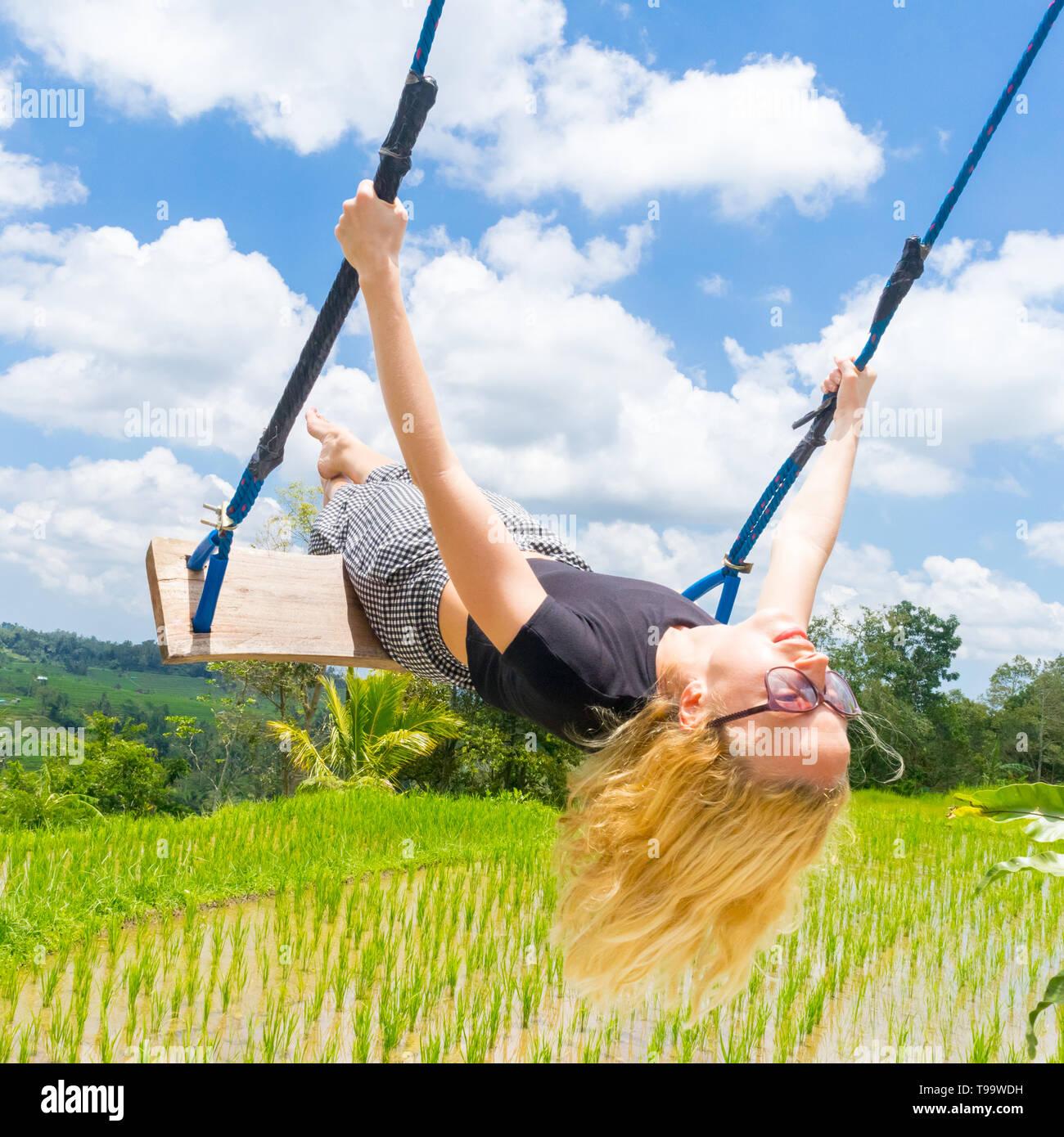Happy female traveller swinging on wooden swing, enjoying summer vacation among pristine green rice terraces. - Stock Image