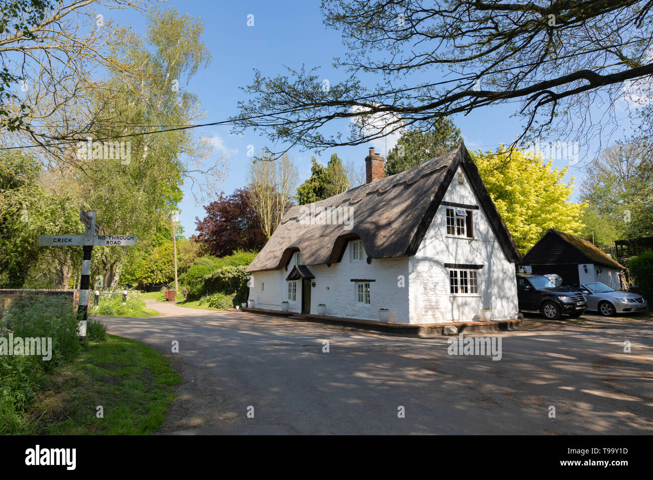 Bridge Cottage, a picturesque, Grade II listed, thatched building stands at a crossroads in the small and pretty Northamptonshire village of Winwick. - Stock Image