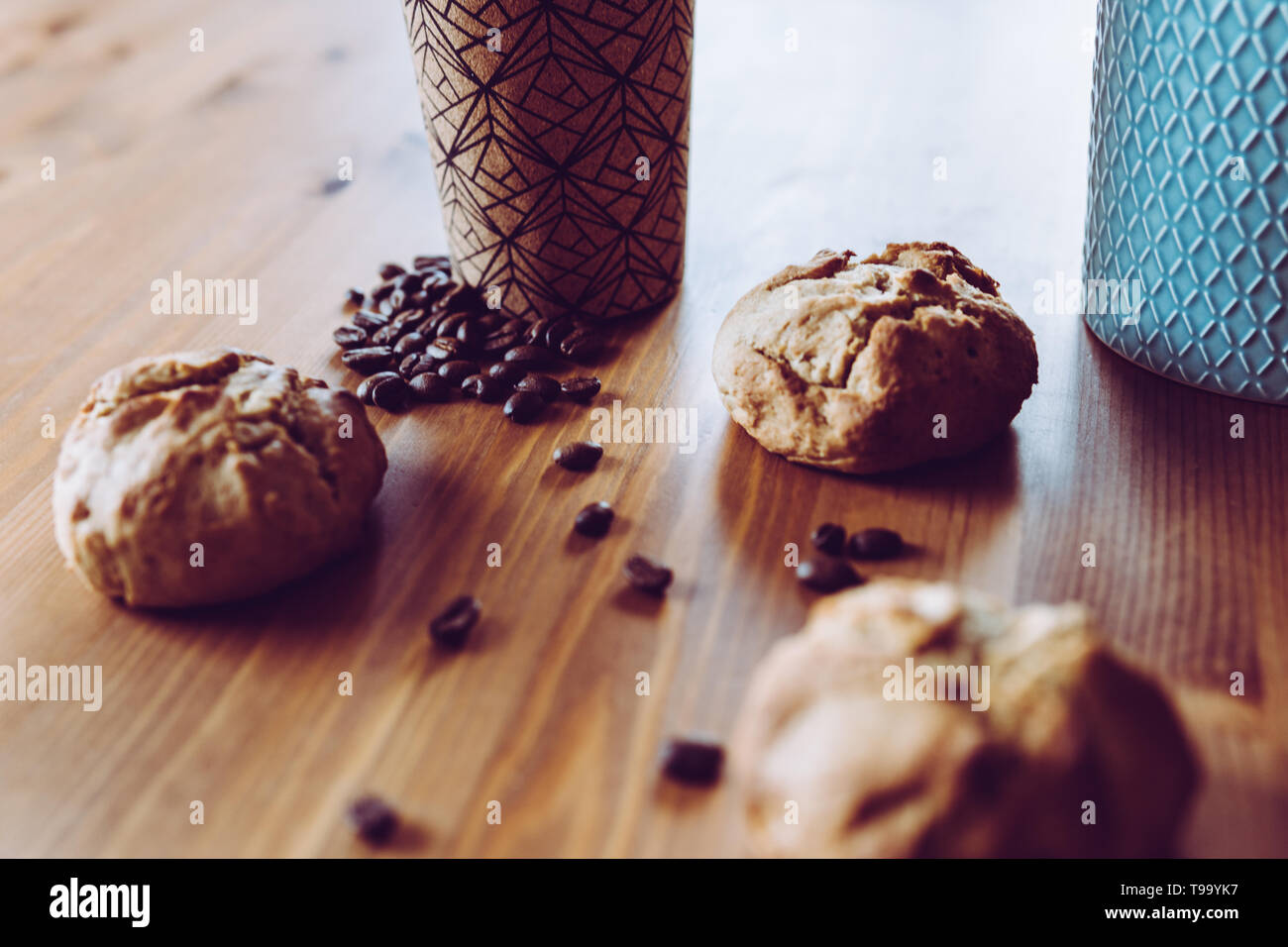 Three homemade vegan bread rolls, freshly roasted coffee beans, one coffee to go cup and teal ceramic can on a wooden table (close-up, focus on beans) - Stock Image