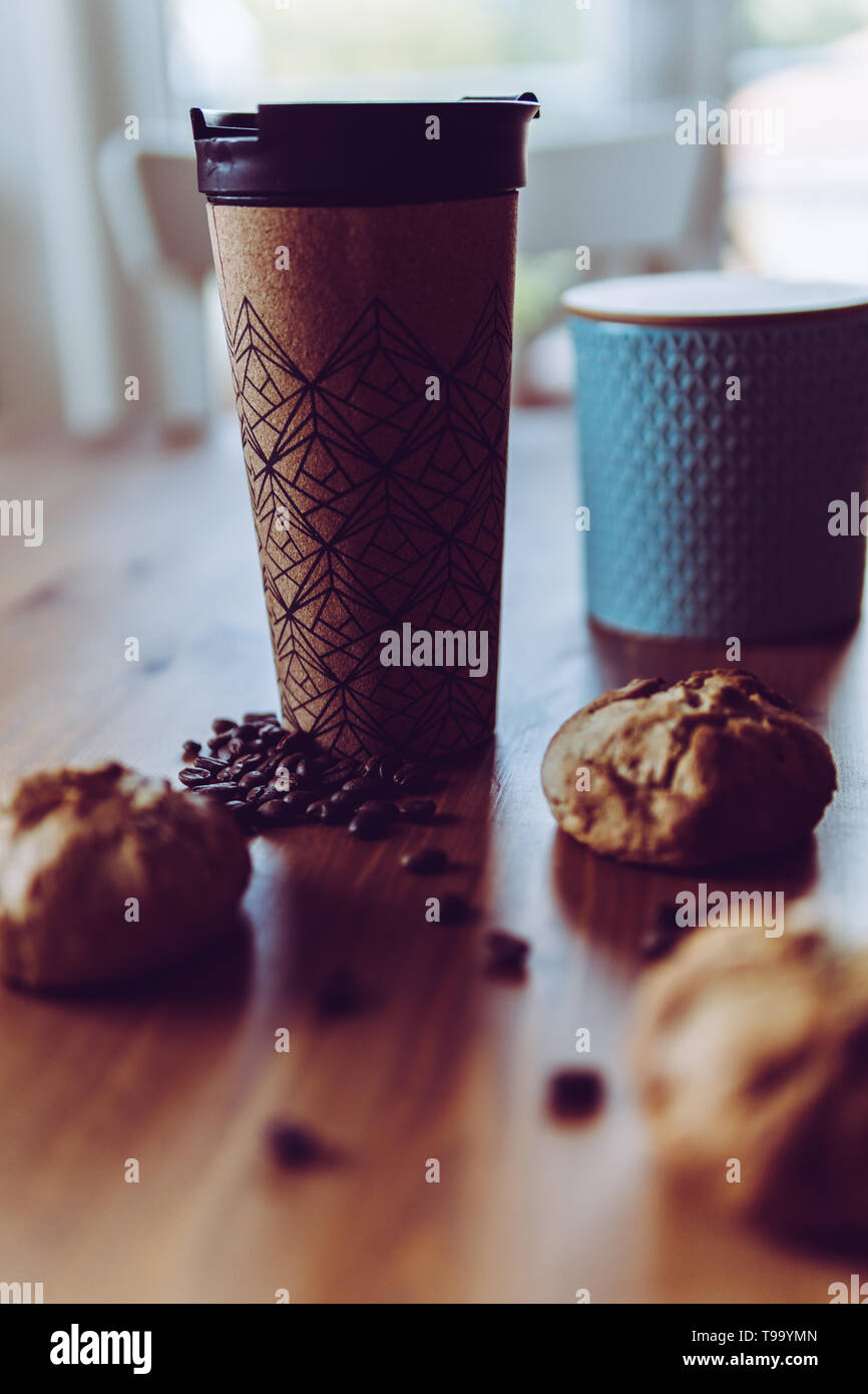Breakfast on the go for the commute: Coffee to-go and three homemade vegan bread rolls, decorated with roasted coffee beans and teal ceramic can - Stock Image