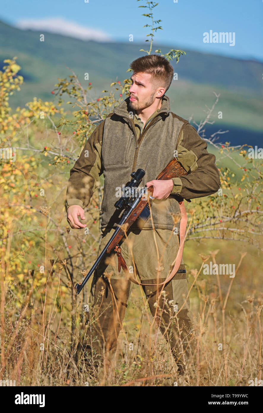 Hunter bearded poacher looking for victim. Poacher with rifle in nature environment. Illegal hunting. Forbidden hunting. Breaking law. Poaching concept. Activity for brutal man. Hunter brutal poacher. - Stock Image
