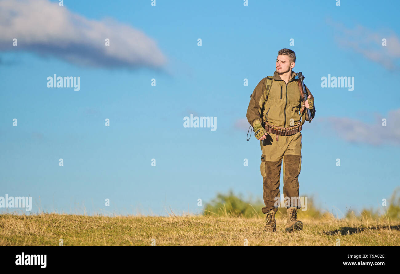 Hunting weapon gun or rifle. Hunting hobby. Guy hunting nature environment. Masculine hobby activity. Man hunter carry rifle blue sky background. Experience and practice lends success hunting. - Stock Image
