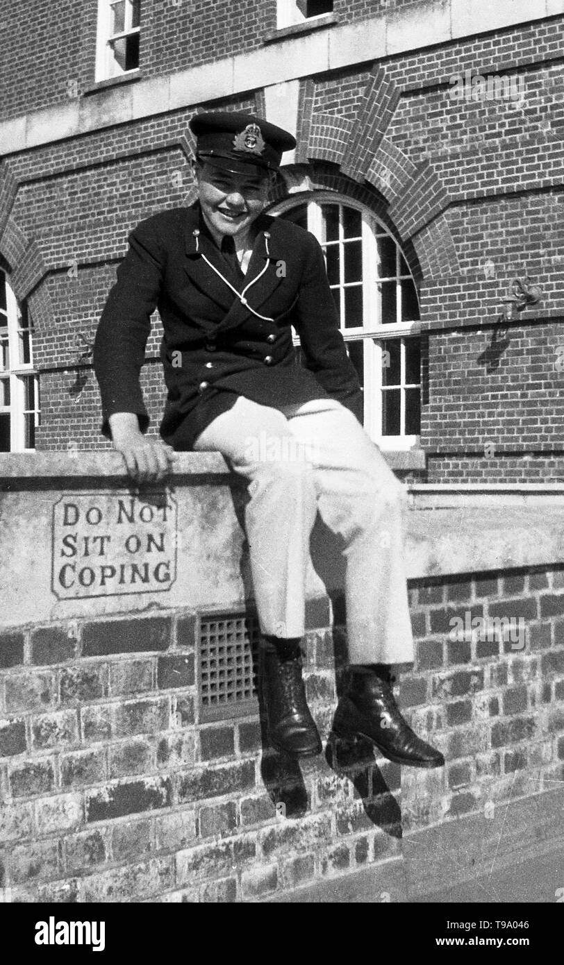A Boy in Smart Uniform Breaking The Rules by sitting on a wall by a sign that says 'Do Not Sit On Coping'. Photo by Tony Henshaw - Stock Image