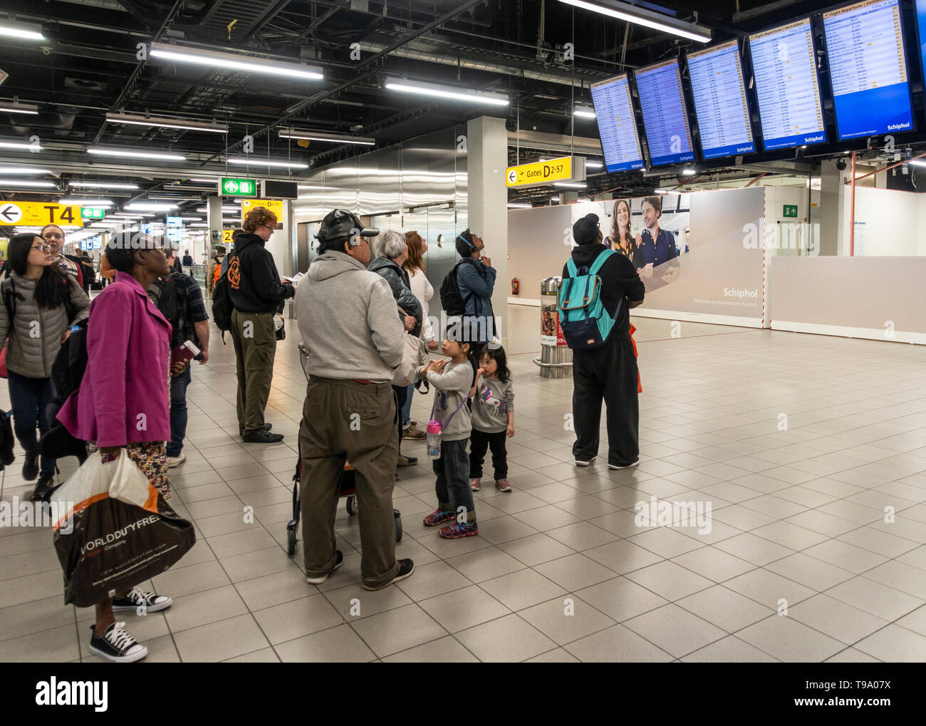 Passengers checking the departures board at Schiphol Airport, Amsterdam, the Netherlands. Travellers, passengers, travel. - Stock Image
