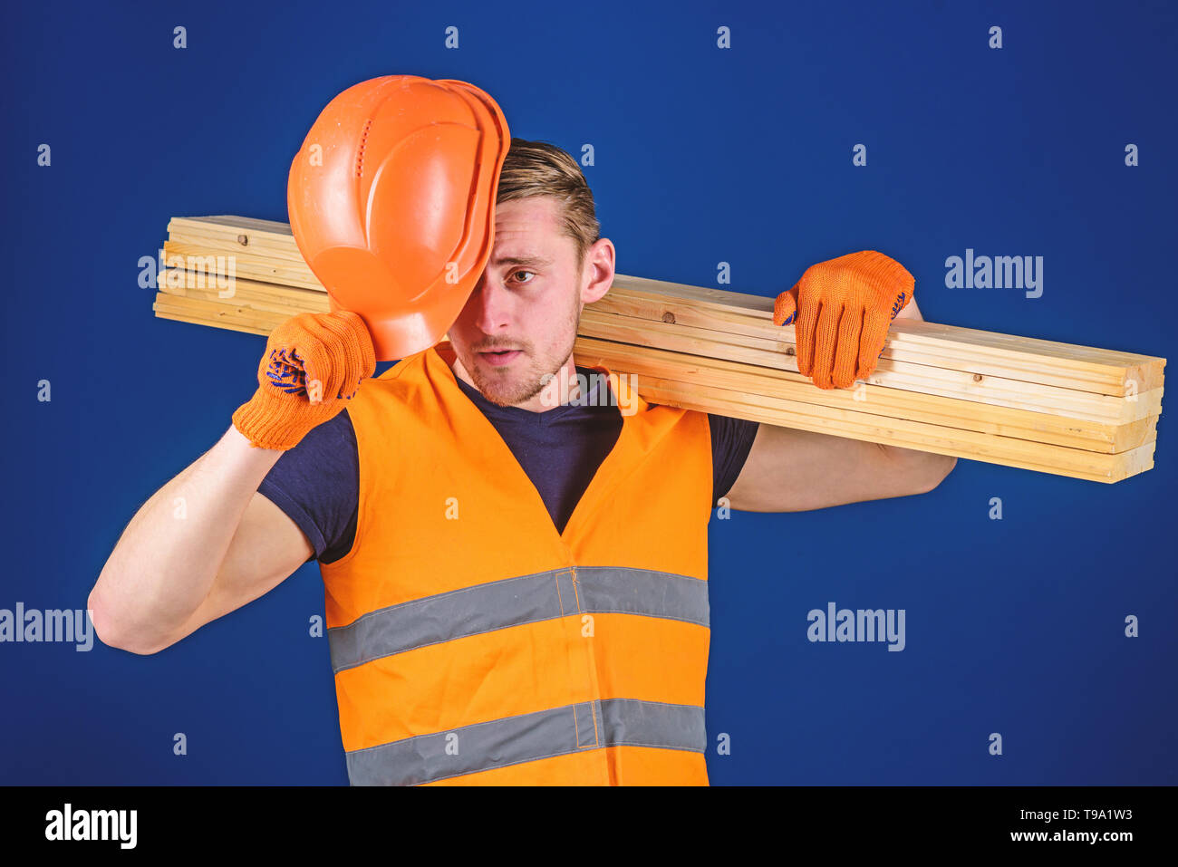 Protective equipment concept. Carpenter, woodworker, labourer, builder carries wooden beam on shoulder. Man in protective gloves holds visor of helmet, corrects hard hat on head, blue background. Stock Photo