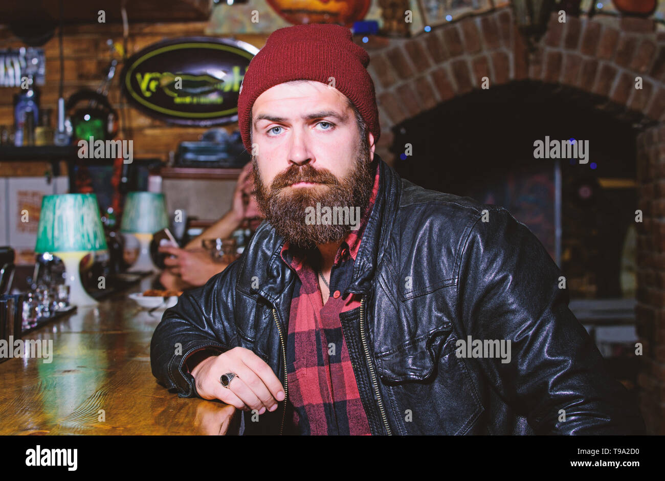 Friday evening. Hipster relaxing at bar. Bar is relaxing place to have drink and relax. Man with beard spend leisure in dark bar. Brutal lonely hipster. Brutal hipster bearded man sit at bar counter. - Stock Image