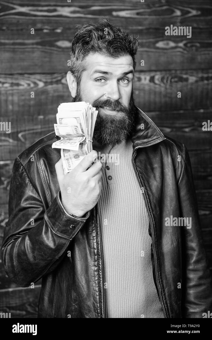 Richness and wellbeing. Man brutal bearded hipster wear leather jacket and hold cash money. Mafia business. Illegal profit and black cash. Guy mafia dealer with cash profit. Brutal man has cash money. - Stock Image