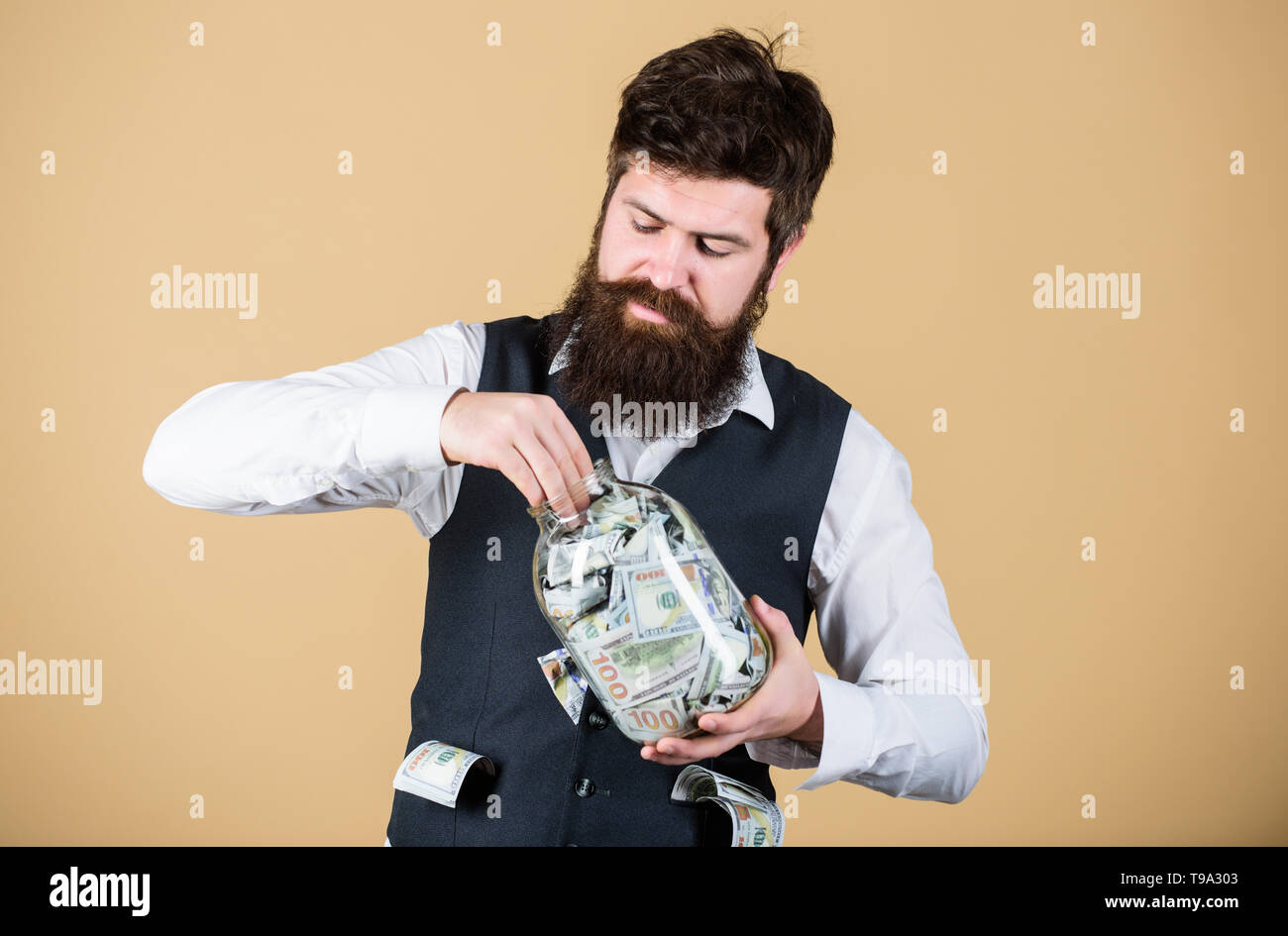 Making an investment. Businessman taking cash money out of glass jar for investing activities. Bearded man investing money into startup business. Investing for future benefit. Investing capitalist. Stock Photo