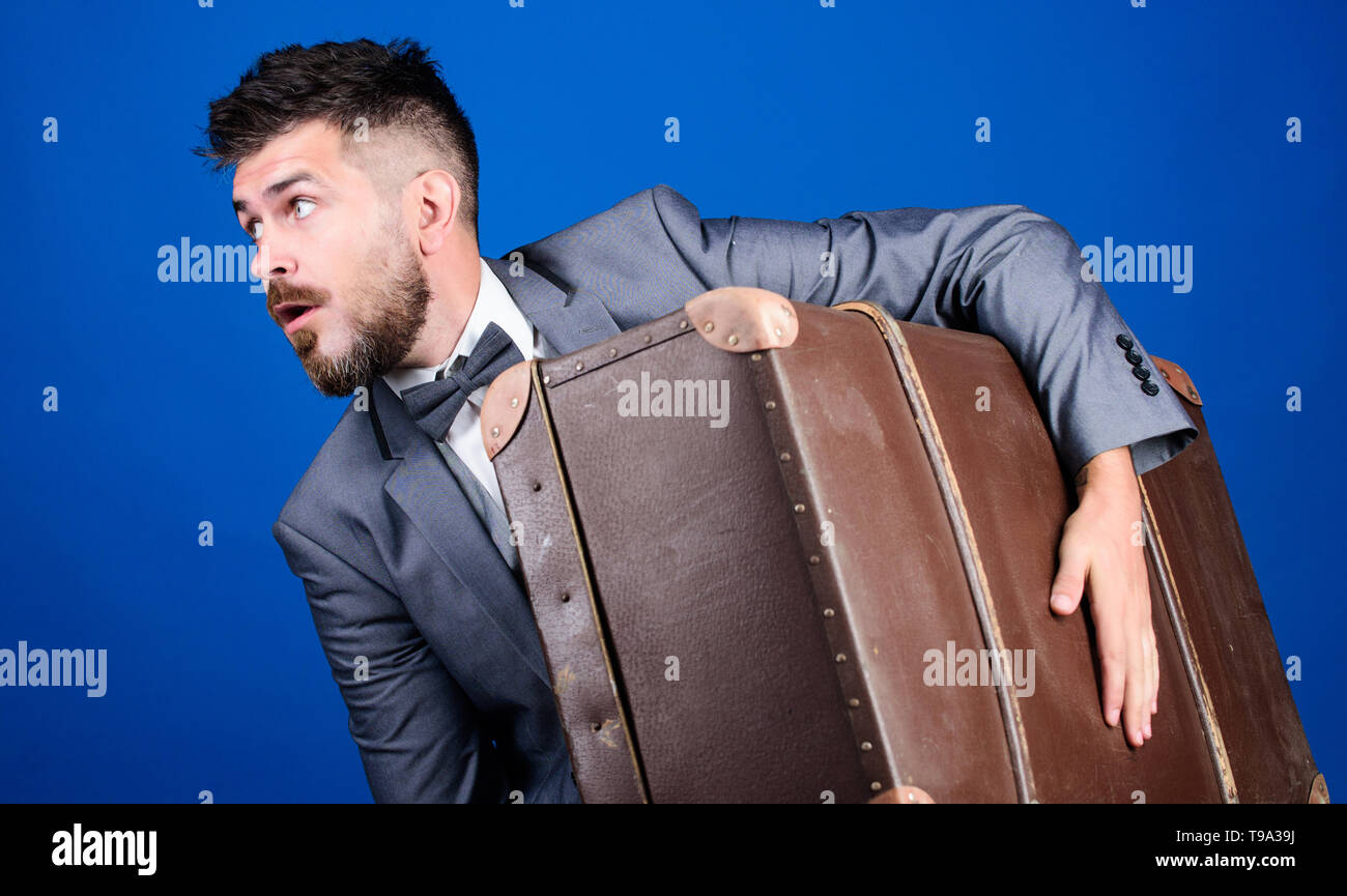 business trip with retro suitcase. heavy bag. mature traveller. stylish esthete with vintage bag. bearded man in formal suit. surprised businessman in bow tie. Complementing his style with bag. - Stock Image