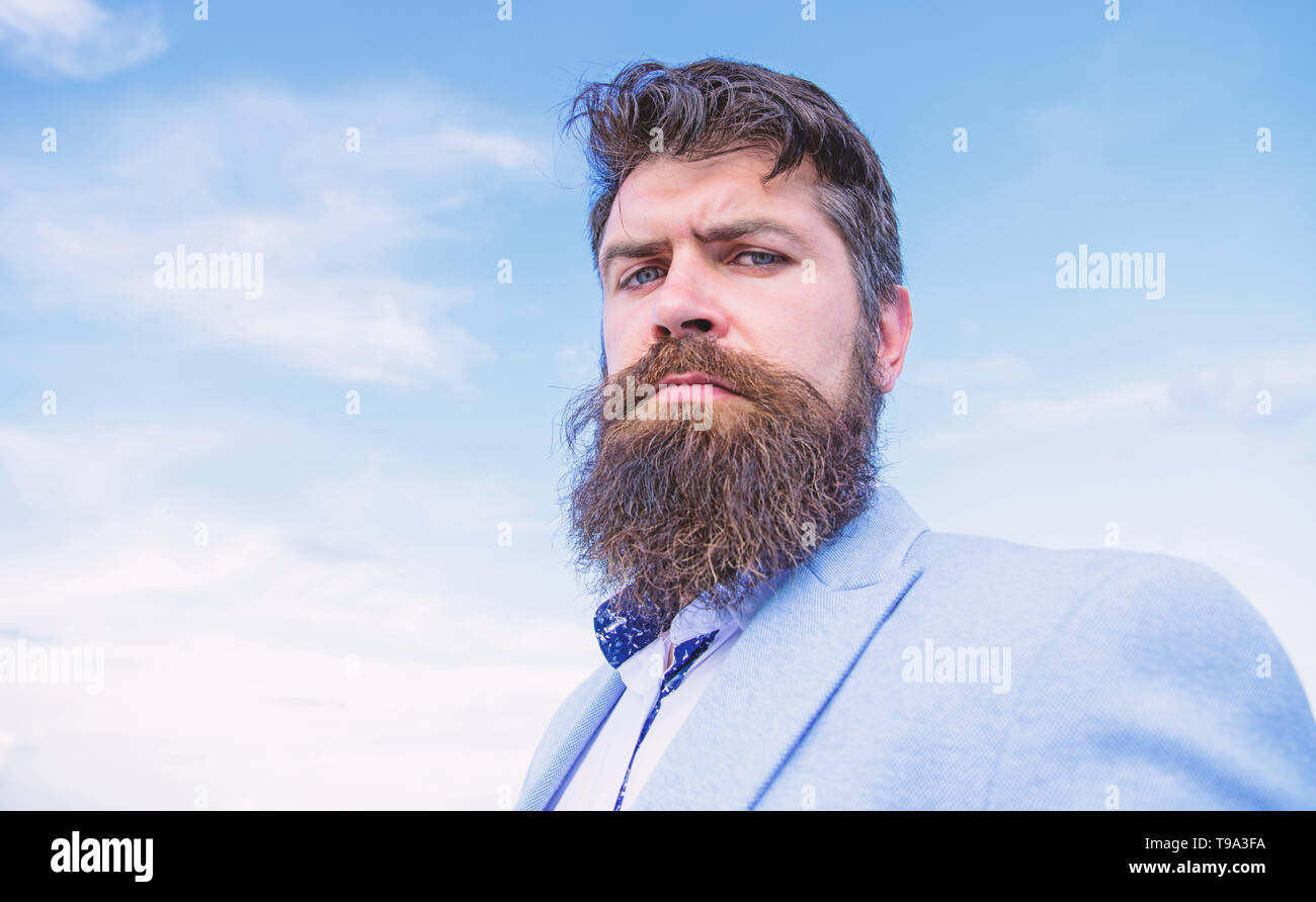 Expert tips for growing and maintaining mustache. Hipster serious handsome attractive guy with long beard. Ultimate mustache grooming guide. Man bearded hipster with mustache blue sky background. - Stock Image