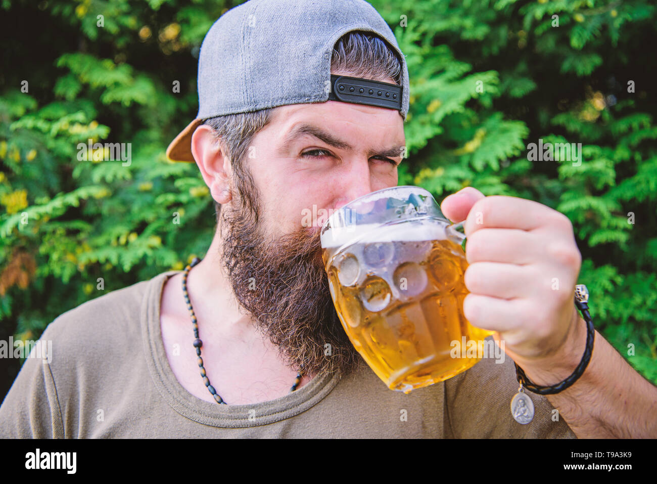 Quench thirst. Man relaxing enjoying beer hot summer day. Hipster brutal bearded man hold mug cold fresh beer. Alcohol drink and bar. Craft beer is young, urban and fashionable. Beer and ale concept. - Stock Image