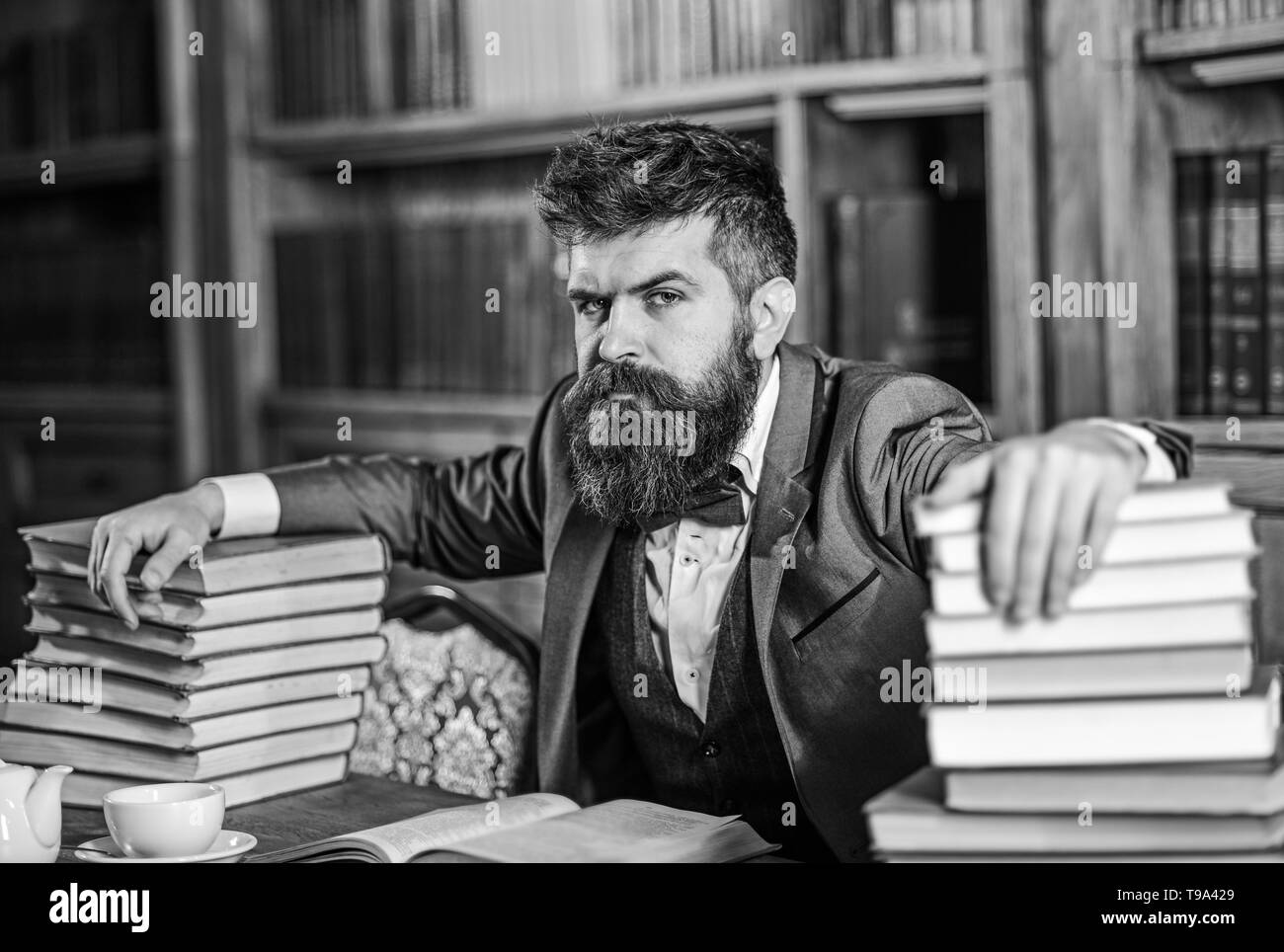 Man sits at table with many books. Mature man has serious face and looks confident. Successful study, education, hard work, intellectual work, confidence, research concept. Guy reads in old library. - Stock Image