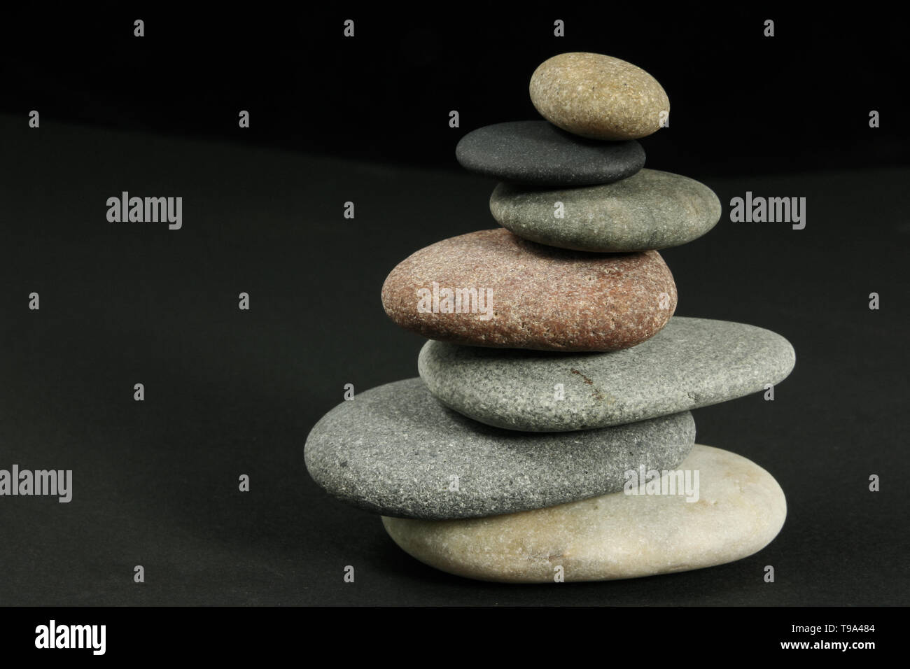 Seven pebbles pyramid in staggered rows, over dark - Stock Image