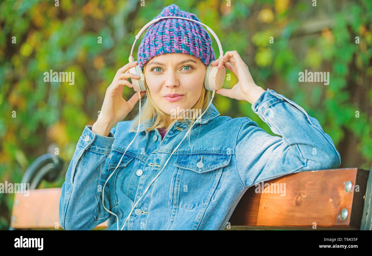 electronic book concept. relax in park. hipster girl with mp3 player. listening music in park. hipster woman in headphones. modern technology instead of reading. electronic book. style and music. - Stock Image