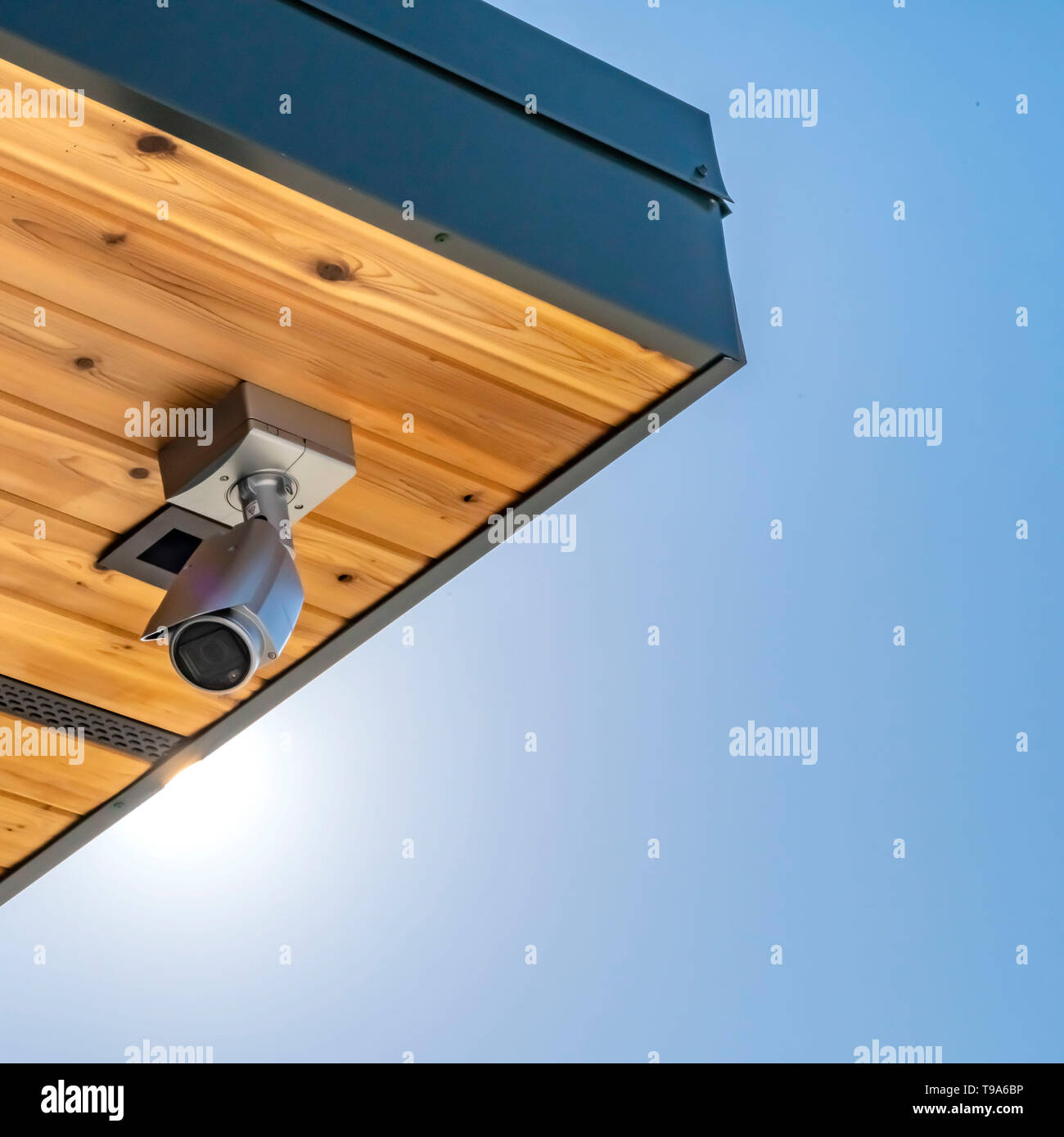Clear Square Home with security camera installed on the wooden underside of its roof - Stock Image