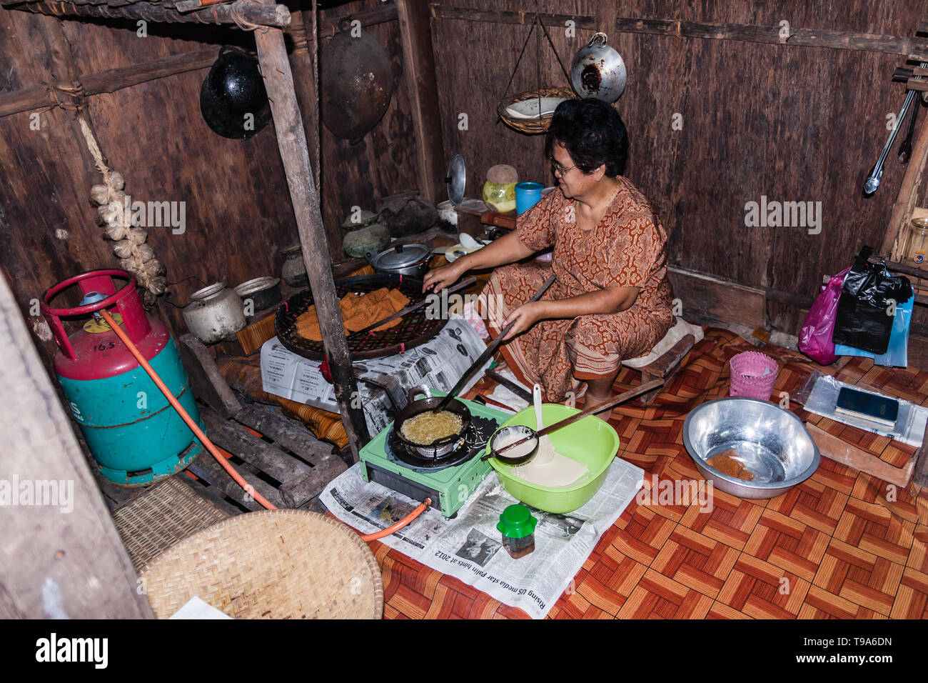 A Malayan woman cooking traditional pancakes in the Iban ethnic house. Sarawak - Stock Image