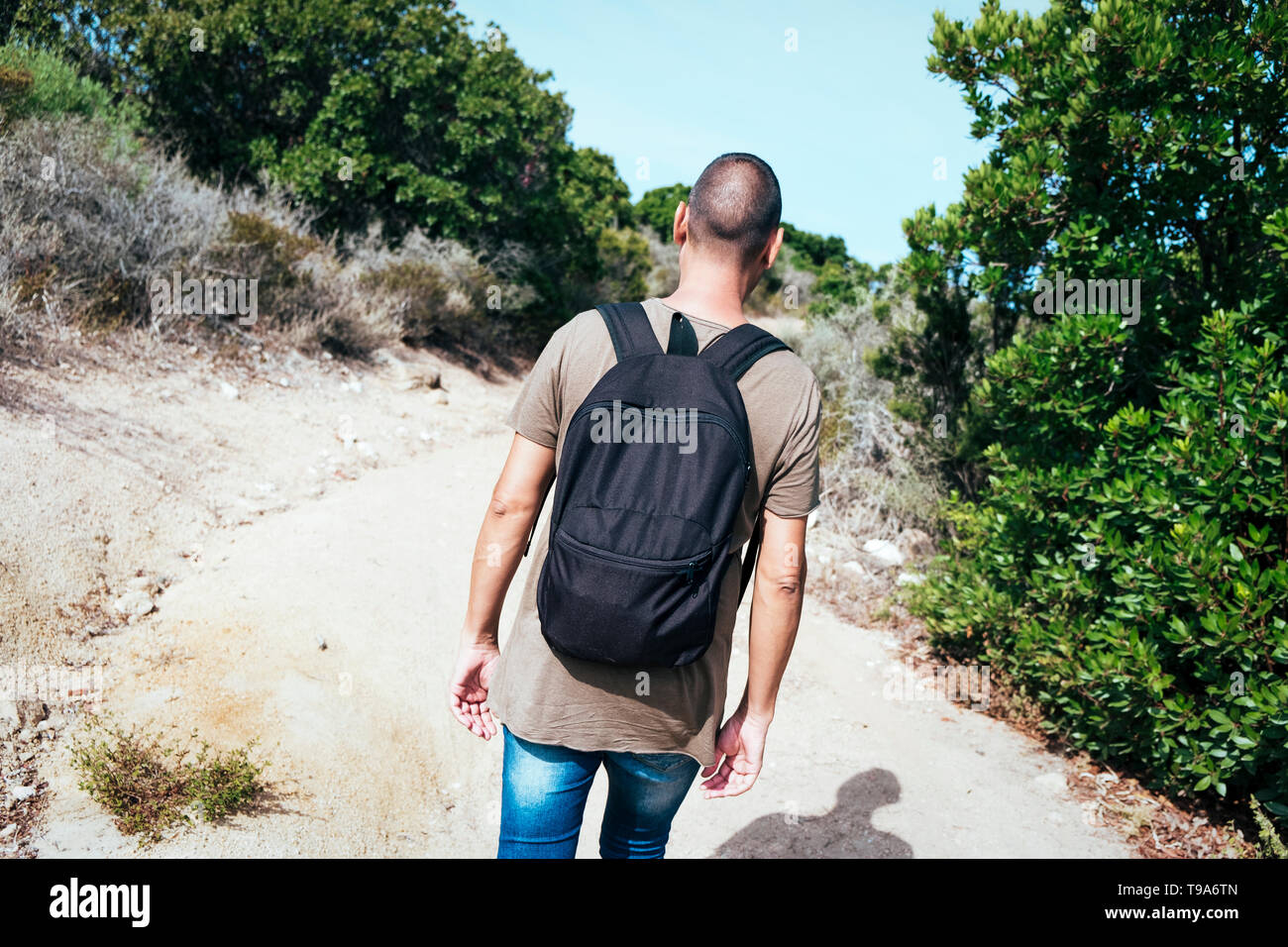 a young caucasian man wearing jeans and a green t-shirt, carrying a backpack, seen from behind, walking by a dirt road - Stock Image