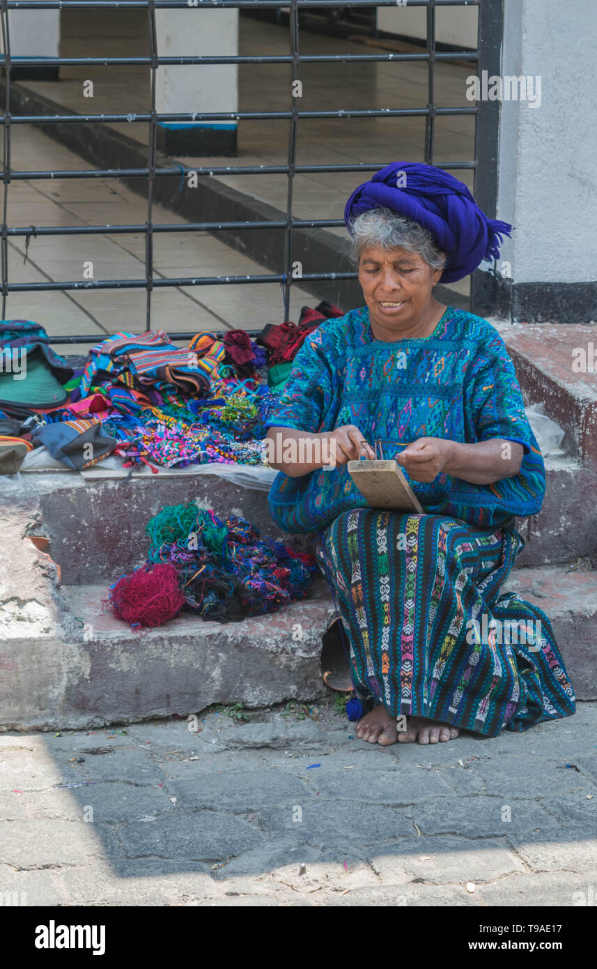 Guatemalan woman in traditional clothing and a blue head scarf sitting on a stone step weaving crafts to sell on the street, in Panajachel, Guatemala Stock Photo