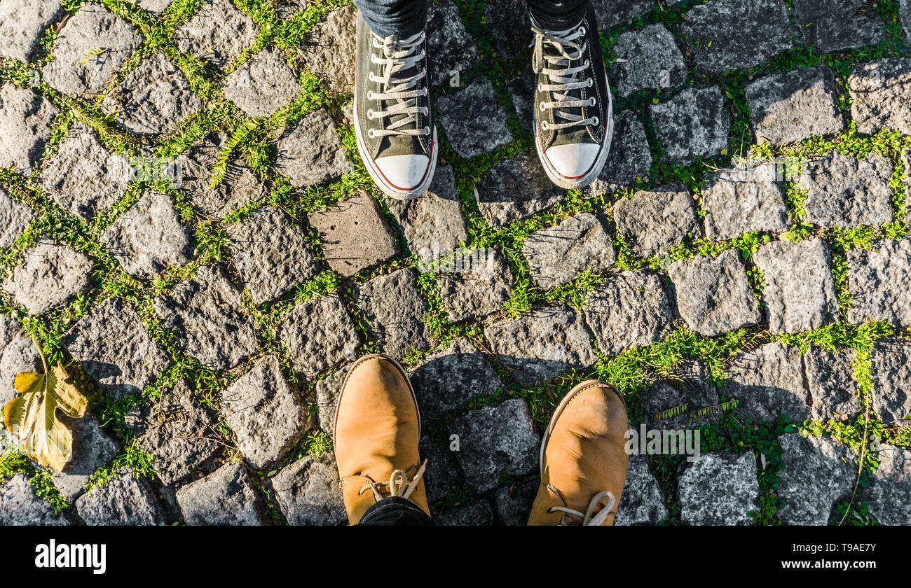 Feet and legs of a happy couple in love against green paving stone background - Stock Image
