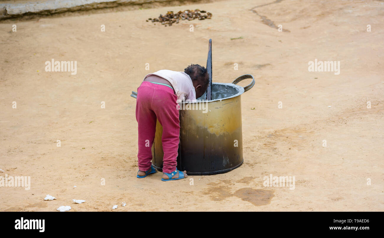 a Malawian child leans over a large metal cooking pot to scrape nsima or porridge from it - Stock Image