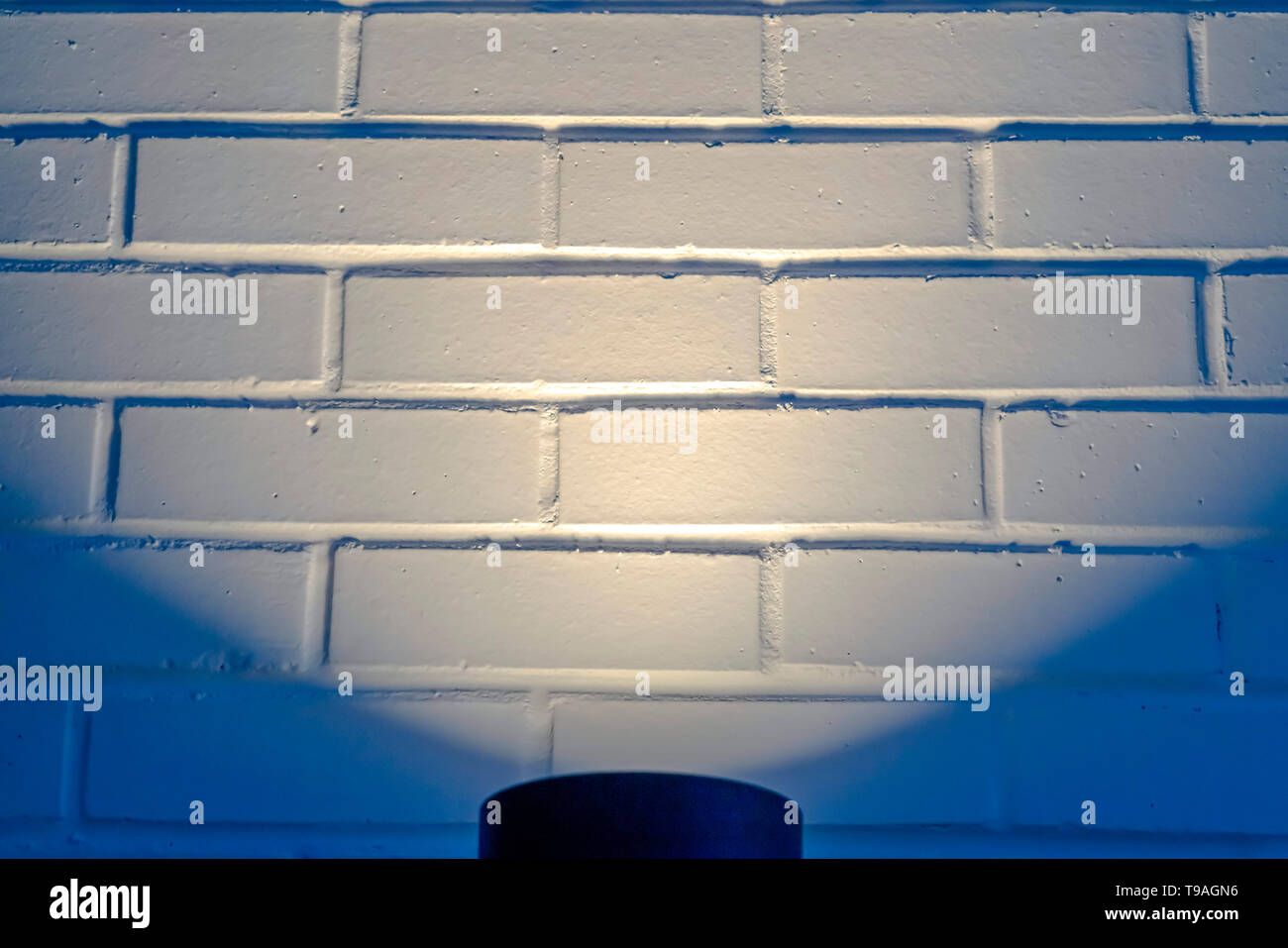 Black cylindrical light illuminating a wall in Eagle Mountain Utah - Stock Image