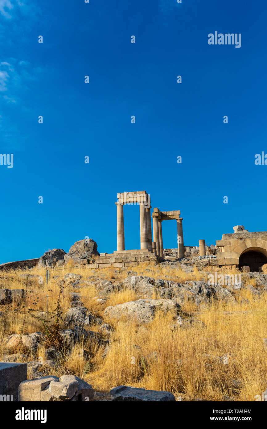 View from below of ancient stone pillars of the acropolis of Lindos, Greece. - Stock Image