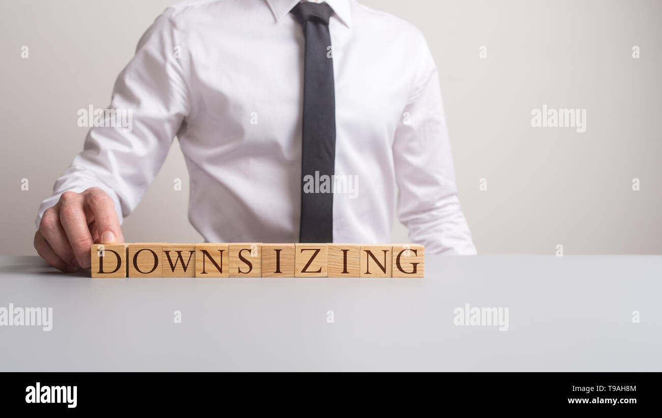 Business executive sitting at his office desk with the sign downsizing in front of him in a conceptual image. - Stock Image