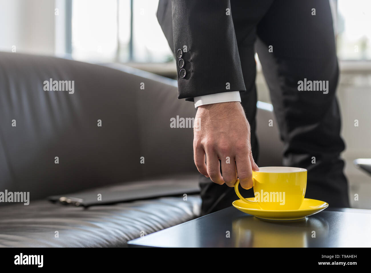 Businessman on a break in his office leaning down toward coffee table to pick up coffee mug as he rest his documents on the couch. - Stock Image