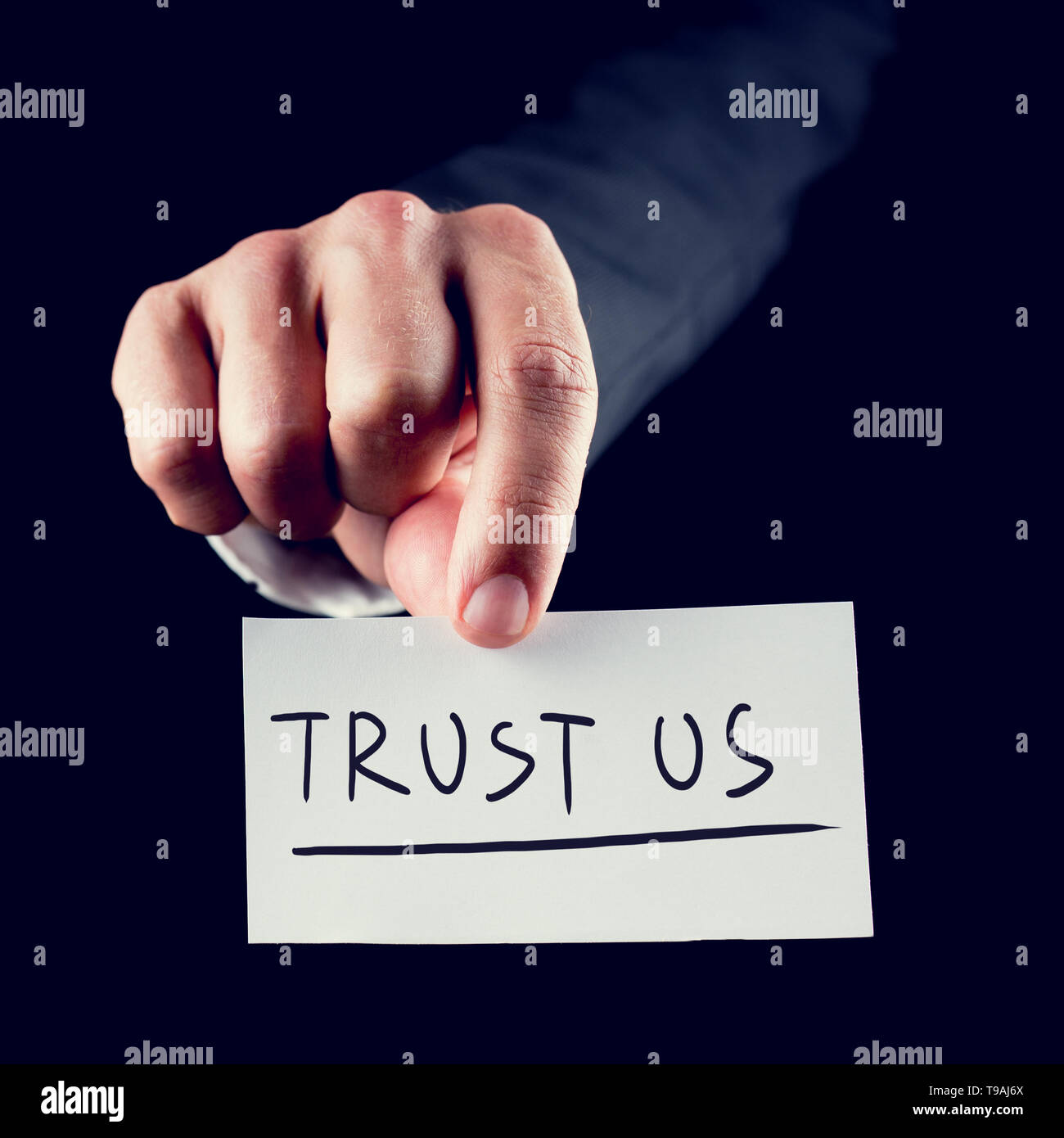 Retro style image of a hand holding piece of paper up close with TRUST US written on it - Stock Image