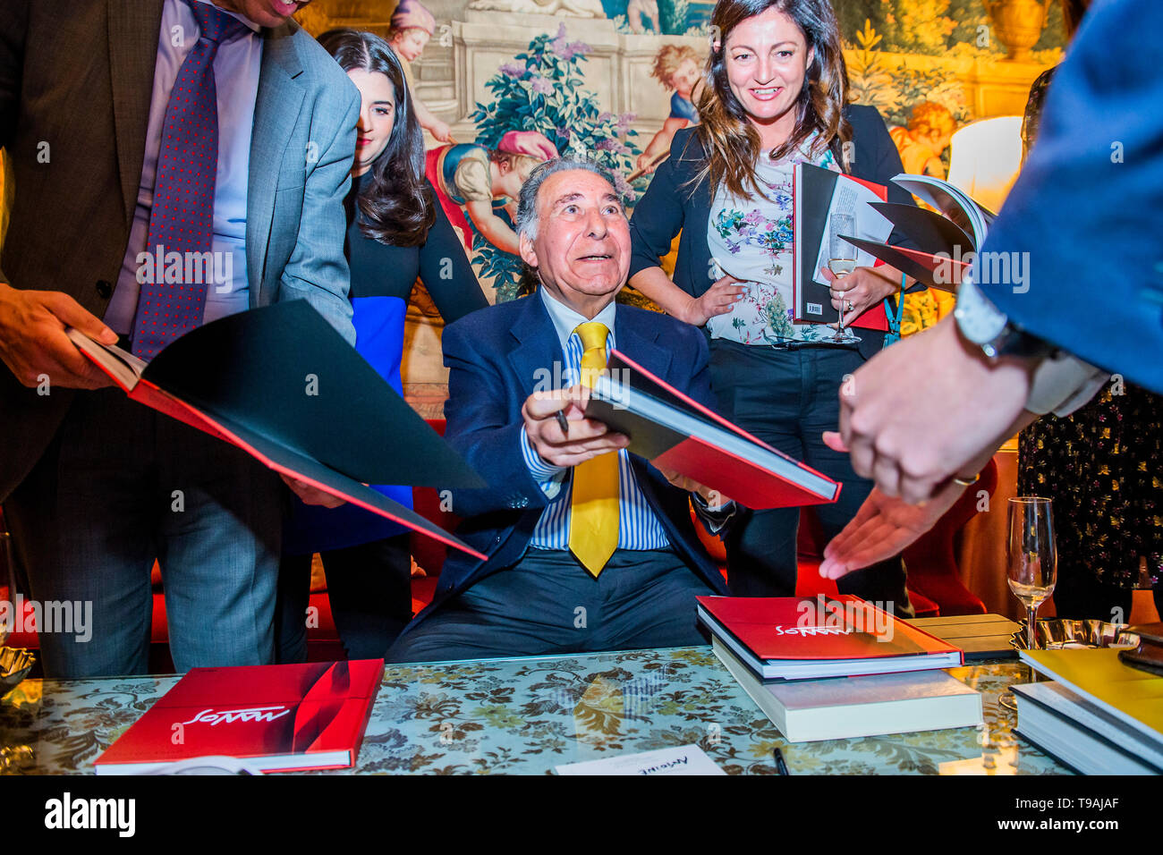 London, UK. 16th May 2019. Pino Manos signs copies of the book of his works - The launch party for Spaziale! at Opera Gallery London at the Italian Embassy.The exhibition includes 40 iconic canvases by Lucio Fontana, Agostino Bonalumi and Enrico Castellani among others. Credit: Guy Bell/Alamy Live News - Stock Image