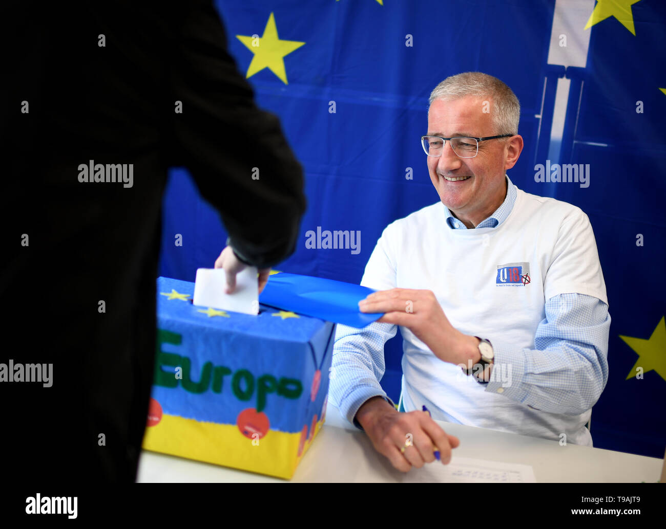 Berlin, Germany. 17th May, 2019. Reinhard Fischer, election worker, receives the ballot papers at a polling station during the U18 European elections. Credit: Britta Pedersen/dpa-Zentralbild/dpa/Alamy Live News Stock Photo