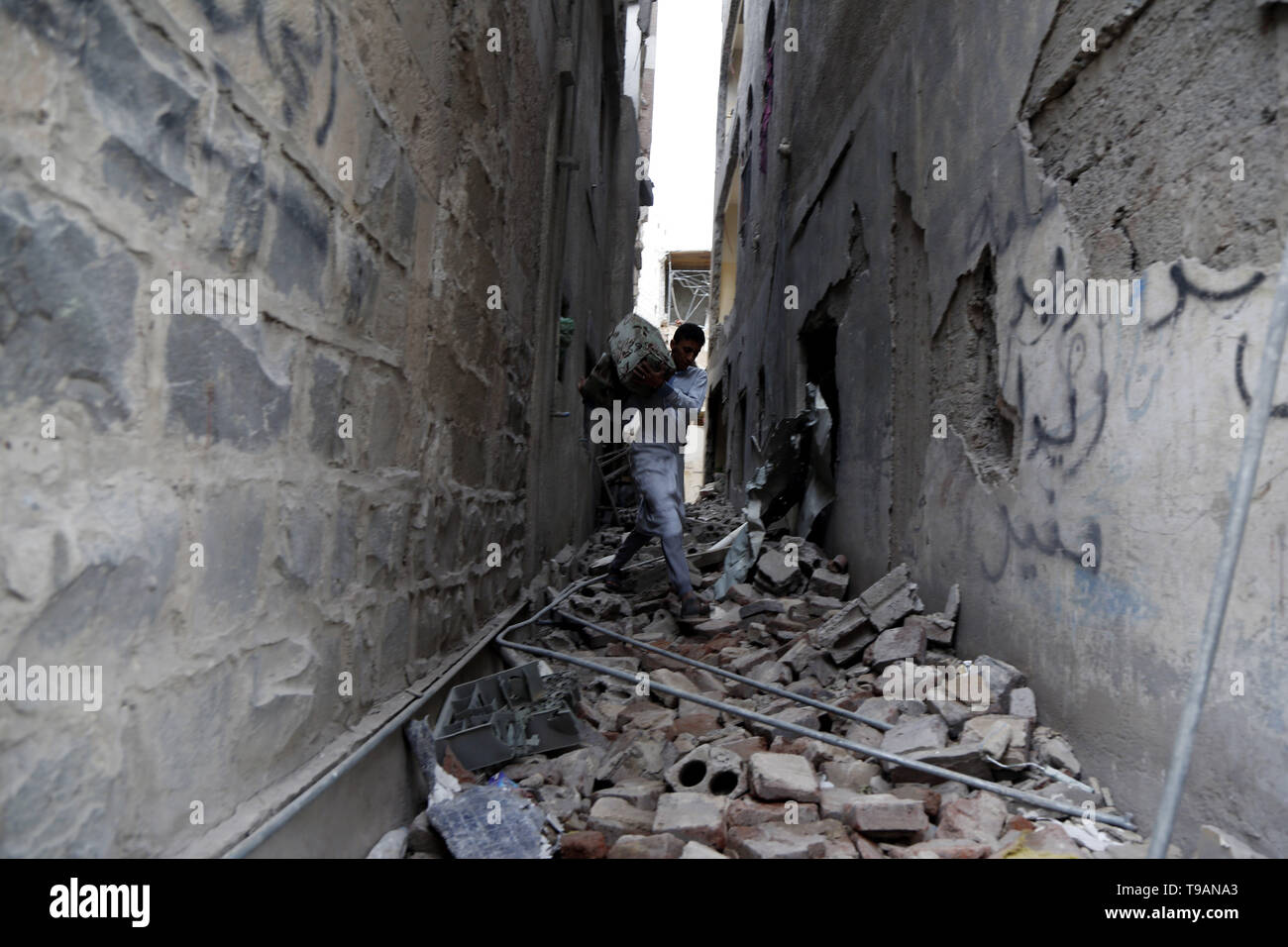 Sanaa, Yemen. 17th May, 2019. A man takes furniture out of a building after it was hit in airstrikes in Sanaa, Yemen, on May 17, 2019. The Saudi Arabia-led coalition launched airstrikes on Houthi rebels' targets in the Yemeni capital Sanaa on Thursday morning, causing civilian casualties and damages, authorities and local residents said. Credit: Mohammed Mohammed/Xinhua/Alamy Live News - Stock Image