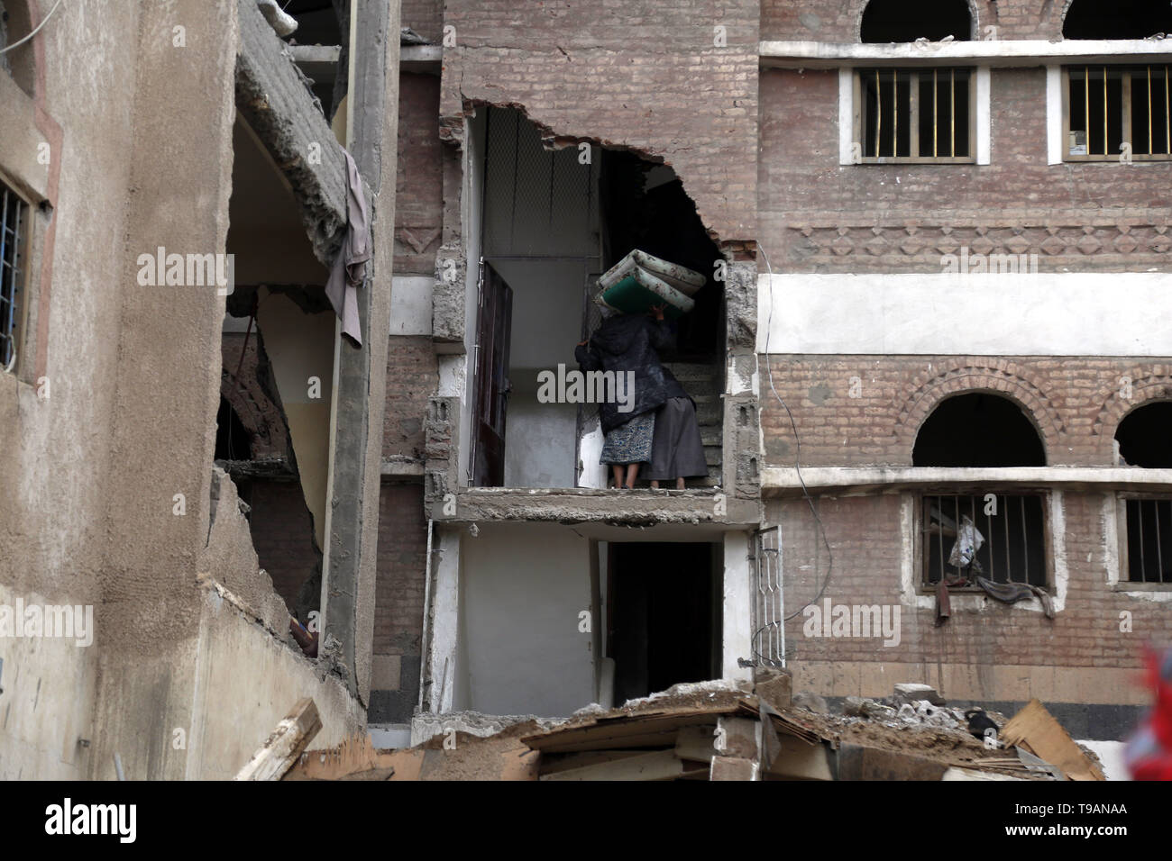 Sanaa, Yemen. 17th May, 2019. People take furniture out of a building after it was hit in airstrikes in Sanaa, Yemen, on May 17, 2019. The Saudi Arabia-led coalition launched airstrikes on Houthi rebels' targets in the Yemeni capital Sanaa on Thursday morning, causing civilian casualties and damages, authorities and local residents said. Credit: Mohammed Mohammed/Xinhua/Alamy Live News - Stock Image