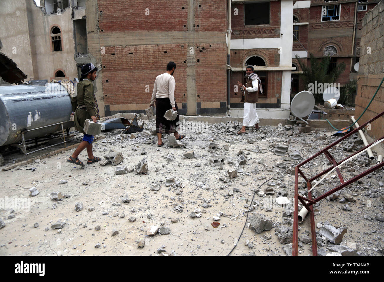 Sanaa, Yemen. 17th May, 2019. People clear debris after airstrikes hit the area in Sanaa, Yemen, on May 17, 2019. The Saudi Arabia-led coalition launched airstrikes on Houthi rebels' targets in the Yemeni capital Sanaa on Thursday morning, causing civilian casualties and damages, authorities and local residents said. Credit: Mohammed Mohammed/Xinhua/Alamy Live News - Stock Image