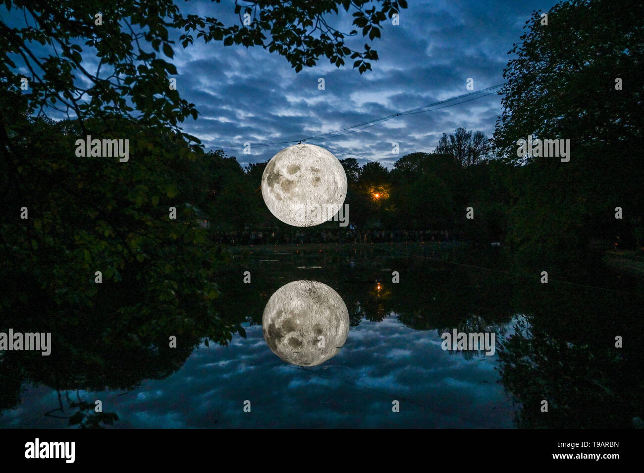 Brighton UK 17th Apr 2019 - Crowds gathered around Queens Park pond in Brighton this evening to watch the Brighton Festival event 'Museum of the Moon' by artist Luke Jerram . The moon will be lit up over the weekend accompanied by music by composer Dan Jones . Credit: Simon Dack / Alamy Live News - Stock Image