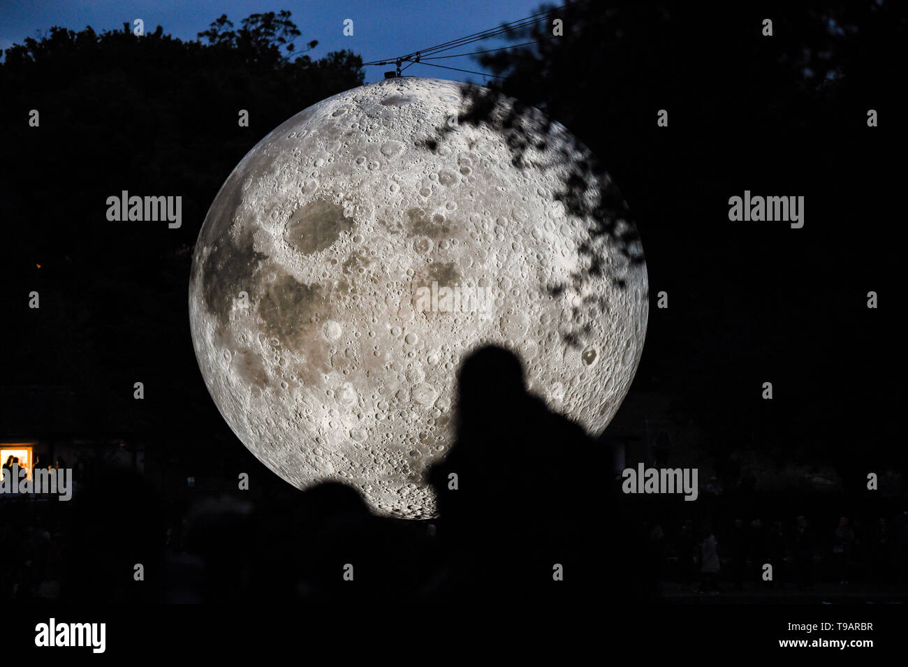 Brighton UK 17th Apr 2019 - Crowds gathered around Queens Park pond in Brighton this evening to watch the Brighton Festival event 'Museum of the Moon' by artist Luke Jerram which celebrated the 50th anniversary of the moon landing. The moon will be lit up over the weekend accompanied by music by composer Dan Jones . Credit: Simon Dack / Alamy Live News - Stock Image