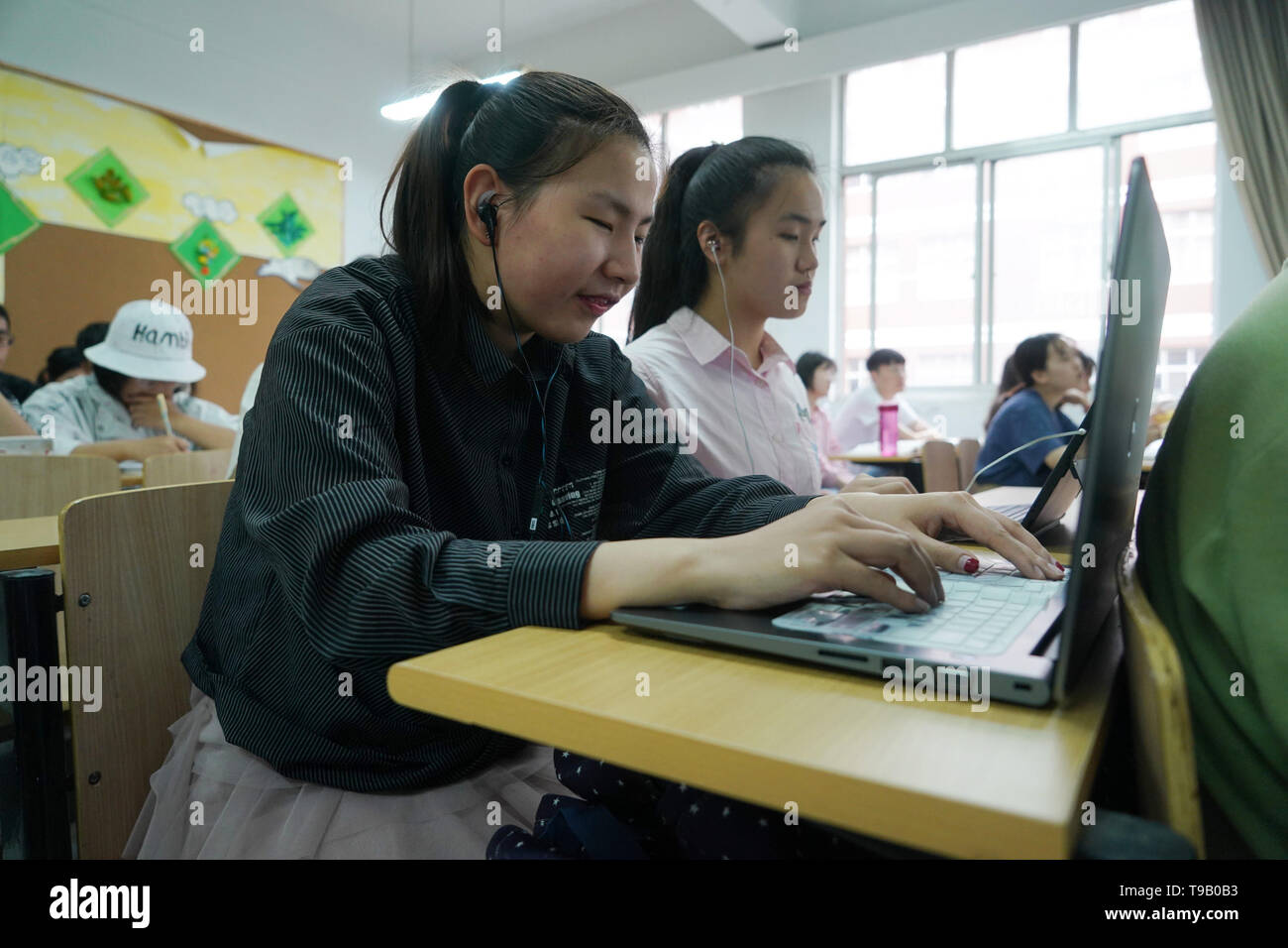 (190518) -- NANJING, May 18, 2019 (Xinhua) -- Wu Yifan(L) and Zhou Wenqing study a professional course in Nanjing Normal University of Special Education in Nanjing, east China's Jiangsu Province, May 17, 2019. Wu Yifan, 22, and Zhou Wenqing, 21, are schoolmates in Nanjing Normal University of Special Education. Both of them lost eyesight in their childhood.   In their spare time, Wu likes doing makeup, paper-cutting as well as playing the Guzheng, Chinese Zither. While Zhou enjoys playing the piano. Zhou once developed a computer game for visually impaired people.   The two girls have passed t - Stock Image