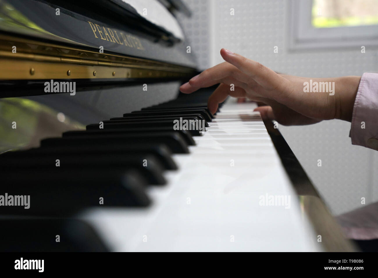 (190518) -- NANJING, May 18, 2019 (Xinhua) -- Zhou Wenqing plays the music composed by herself at the piano room in Nanjing Normal University of Special Education in Nanjing, east China's Jiangsu Province, May 17, 2019. Wu Yifan, 22, and Zhou Wenqing, 21, are schoolmates in Nanjing Normal University of Special Education. Both of them lost eyesight in their childhood.   In their spare time, Wu likes doing makeup, paper-cutting as well as playing the Guzheng, Chinese Zither. While Zhou enjoys playing the piano. Zhou once developed a computer game for visually impaired people.   The two girls hav - Stock Image