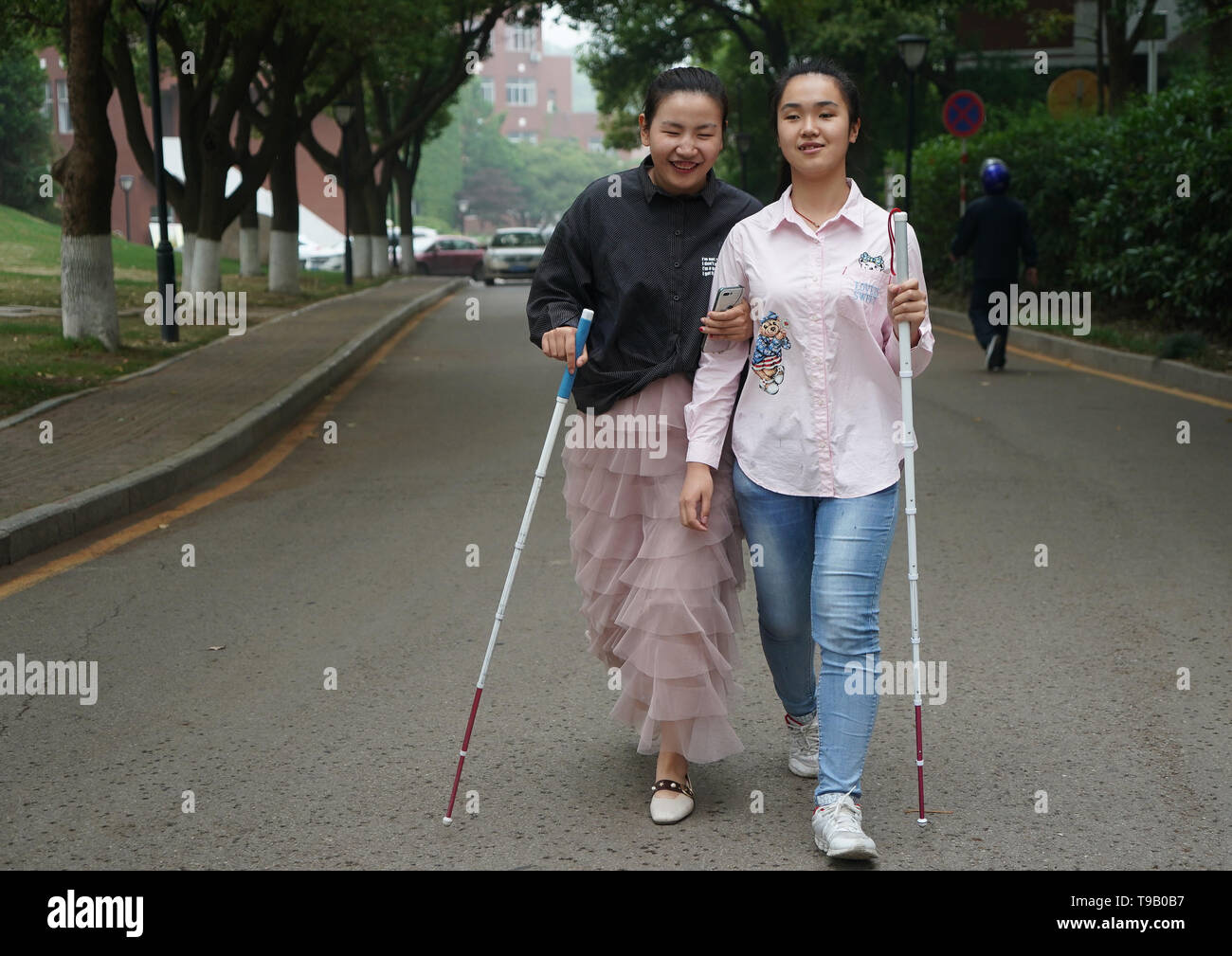 (190518) -- NANJING, May 18, 2019 (Xinhua) -- Wu Yifan(L) and Zhou Wenqing walk along the campus of Nanjing Normal University of Special Education in Nanjing, east China's Jiangsu Province, May 17, 2019. Wu Yifan, 22, and Zhou Wenqing, 21, are schoolmates in Nanjing Normal University of Special Education. Both of them lost eyesight in their childhood.   In their spare time, Wu likes doing makeup, paper-cutting as well as playing the Guzheng, Chinese Zither. While Zhou enjoys playing the piano. Zhou once developed a computer game for visually impaired people.   The two girls have passed the Col - Stock Image