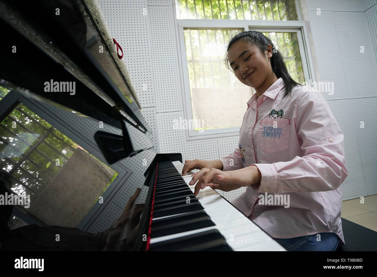 (190518) -- NANJING, May 18, 2019 (Xinhua) -- Zhou Wenqing plays the music composed by herself at the piano room in Nanjing Normal University of Special Education in Nanjing, east China's Jiangsu Province, May 17, 2019. Wu Yifan, 22, and Zhou Wenqing, 21, are schoolmates in Nanjing Normal University of Special Education. Both of them lost eyesight in their childhood. In their spare time, Wu likes doing makeup, paper-cutting as well as playing the Guzheng, Chinese Zither. While Zhou enjoys playing the piano. Zhou once developed a computer game for visually impaired people. The two girls hav Stock Photo