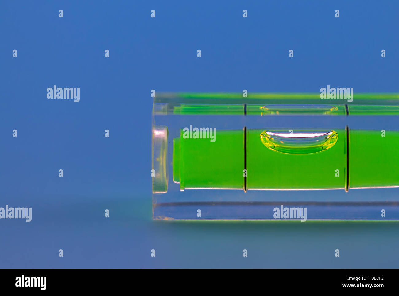 spirit level with green water close up, precise home working diy - Stock Image