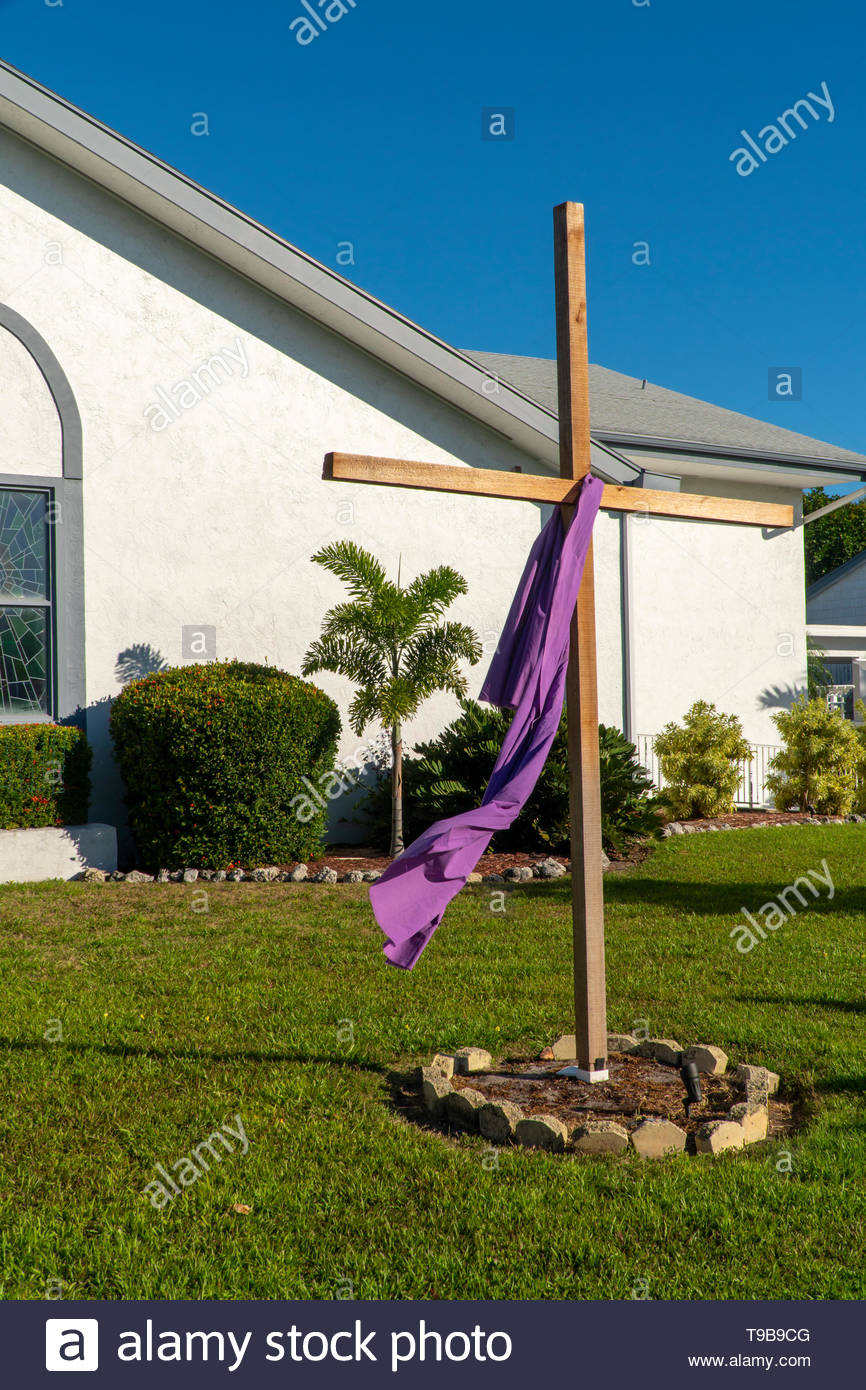 A wooden cross is draped with purple cloth during Easter week on Anna Maria Island, Florida, USA - Stock Image
