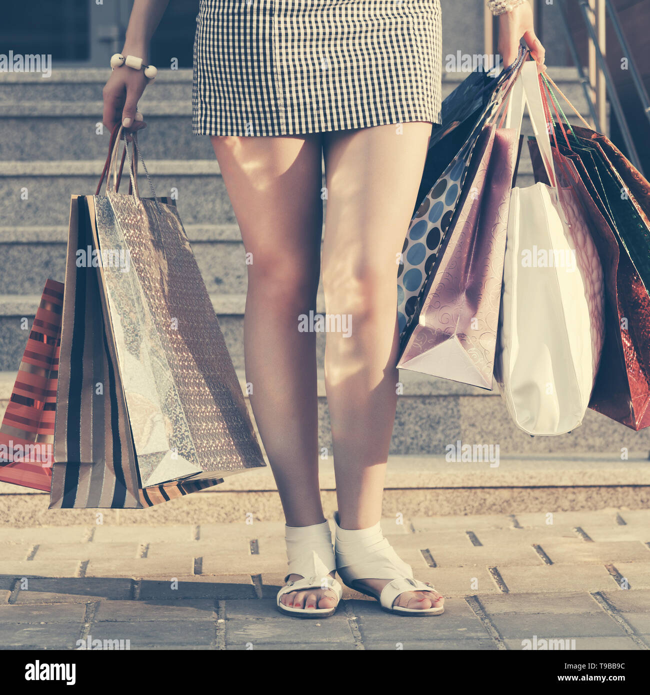 Woman with shopping bags against a mall steps - Stock Image