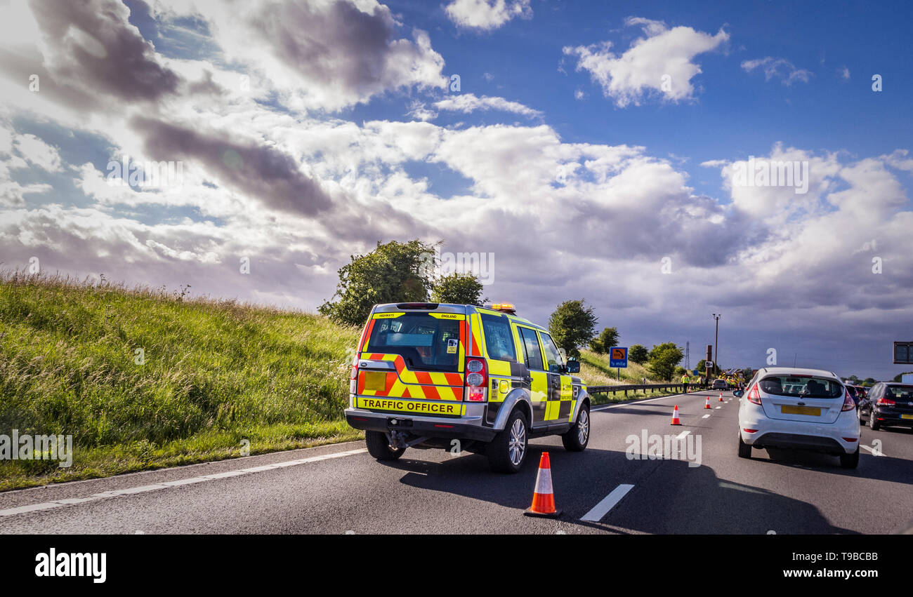 Traffic officer vehicle in closed off lane of motorway due to incident - Stock Image