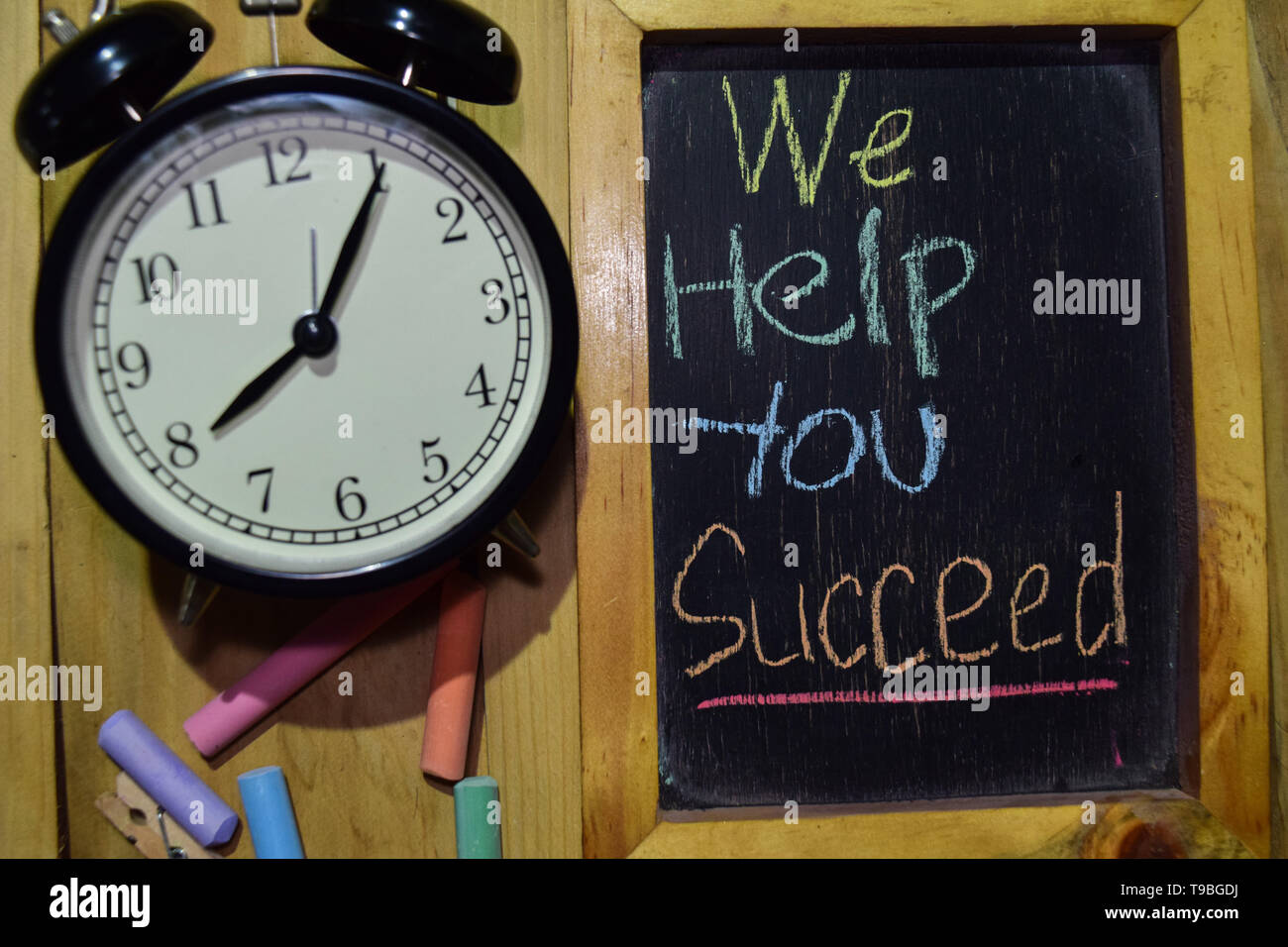 We Help You Succeed on phrase colorful handwritten on chalkboard and alarm clock with motivation, inspiration and education concepts. Table background - Stock Image