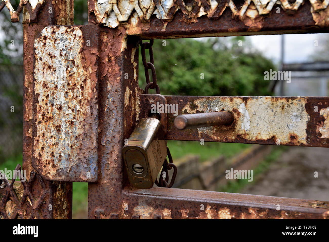 Padlock on rusty outdoor steel security gate with sliding bolt Stock Photo